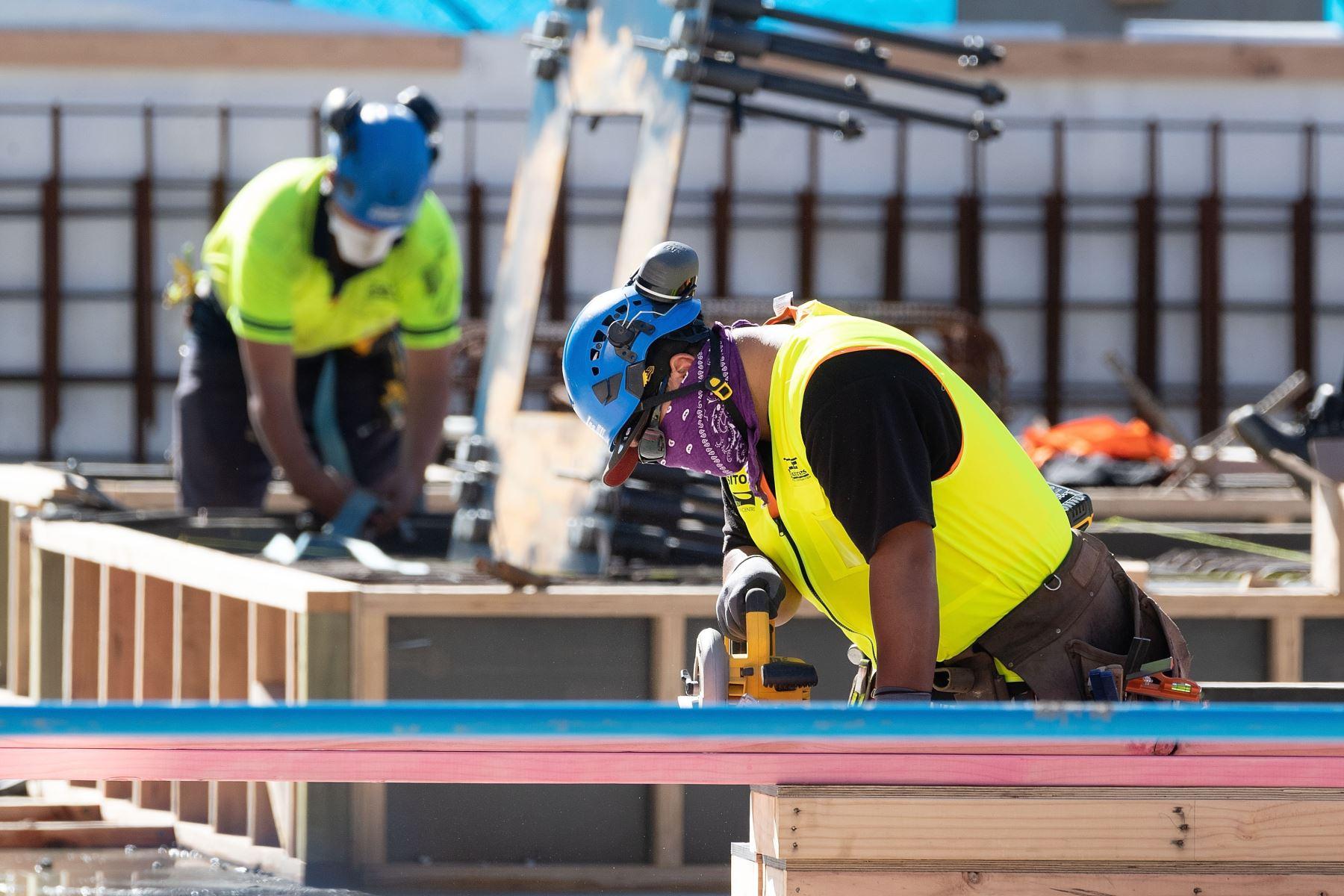 Trabajadores de construcción utilizan mascarillas durante su jornada durante el primer día de la flexibilización de restricciones en Wellington, el 28 de abril de 2020, luego del brote de coronavirus .Foto: AFP