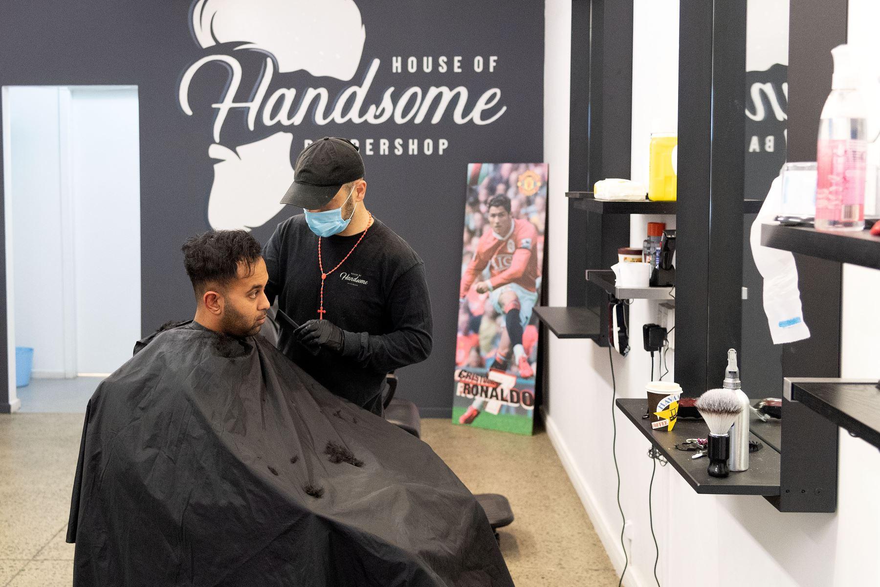 Un peluquero utiliza mascarilla durante su trabajo en la ciudad de Wellington, el 14 de mayo de 2020, en Nueva Zelanda. Foto: AFP