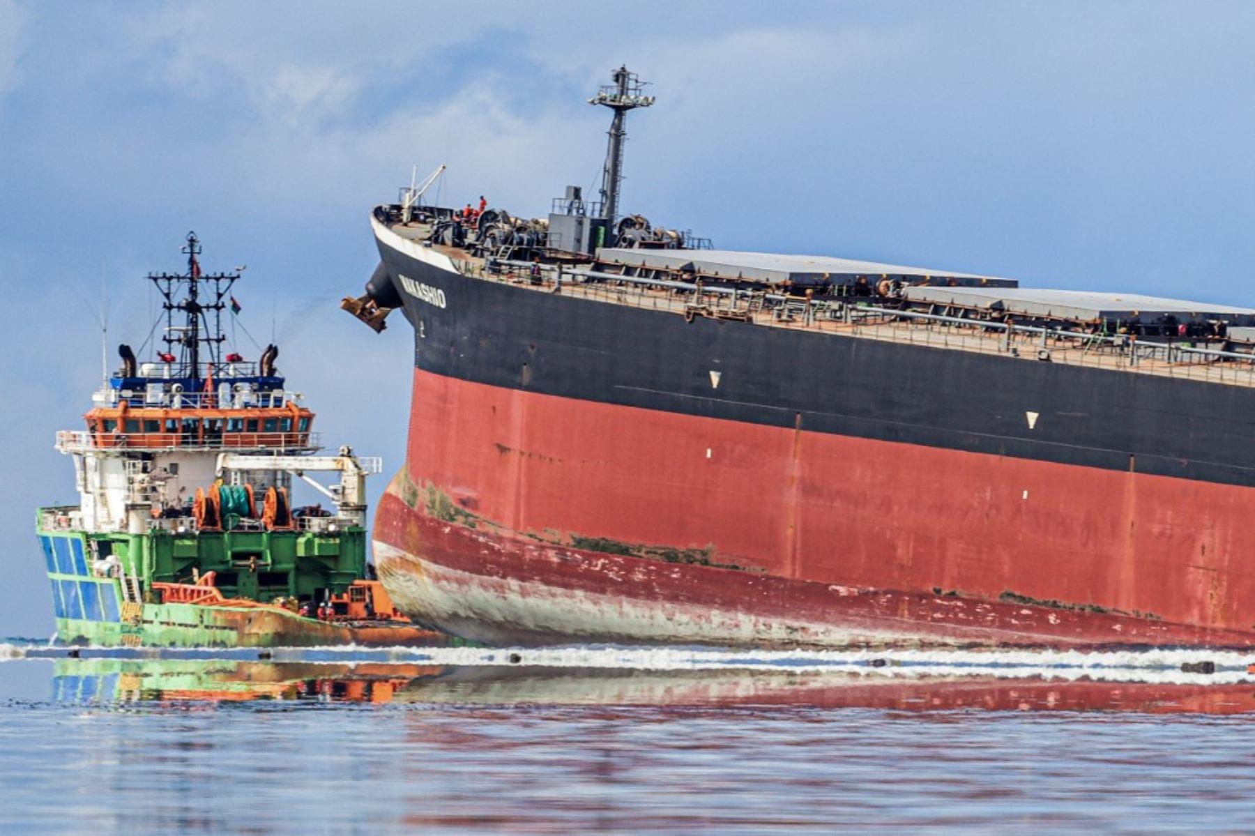 Trabajadores miran desde un barco hacia el buque MV F. responsable del derrame de petróleo. Foto: AFP