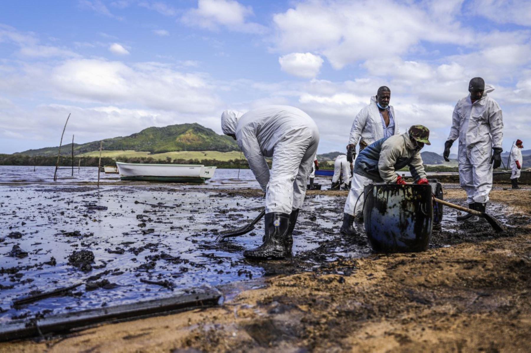 Personas extraen aceite derramado del buque MV Wakashio, perteneciente a una empresa japonesa que encalló y provocó una fuga de petróleo cerca del Blue Bay Marine Park. Foto: AFP