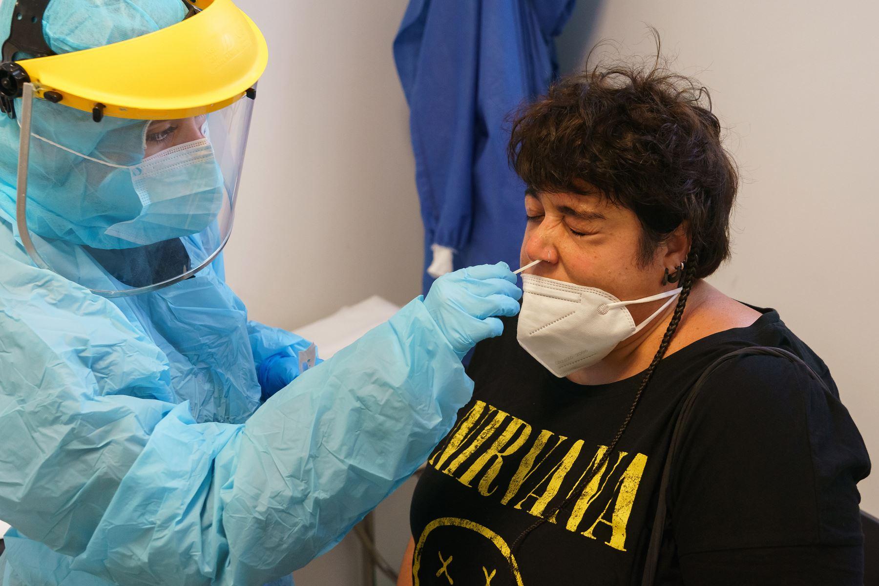 Un trabajador de la salud vestido con equipo de protección toma muestras de una mujer para detectar la enfermedad covid-19 en el centro de salud de La Jota en Zaragoza. Foto: AFP