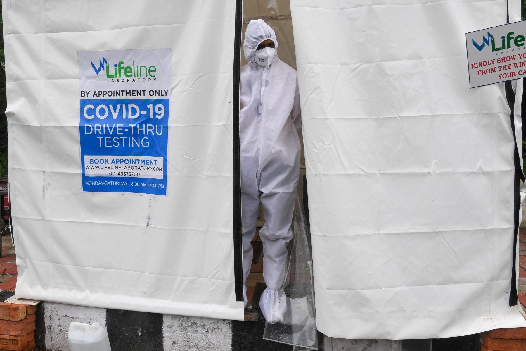 Un trabajador de la salud se asoma desde una caseta improvisada de pruebas de covid -19 junto a una calle en Nueva Delhi . Foto: AFP