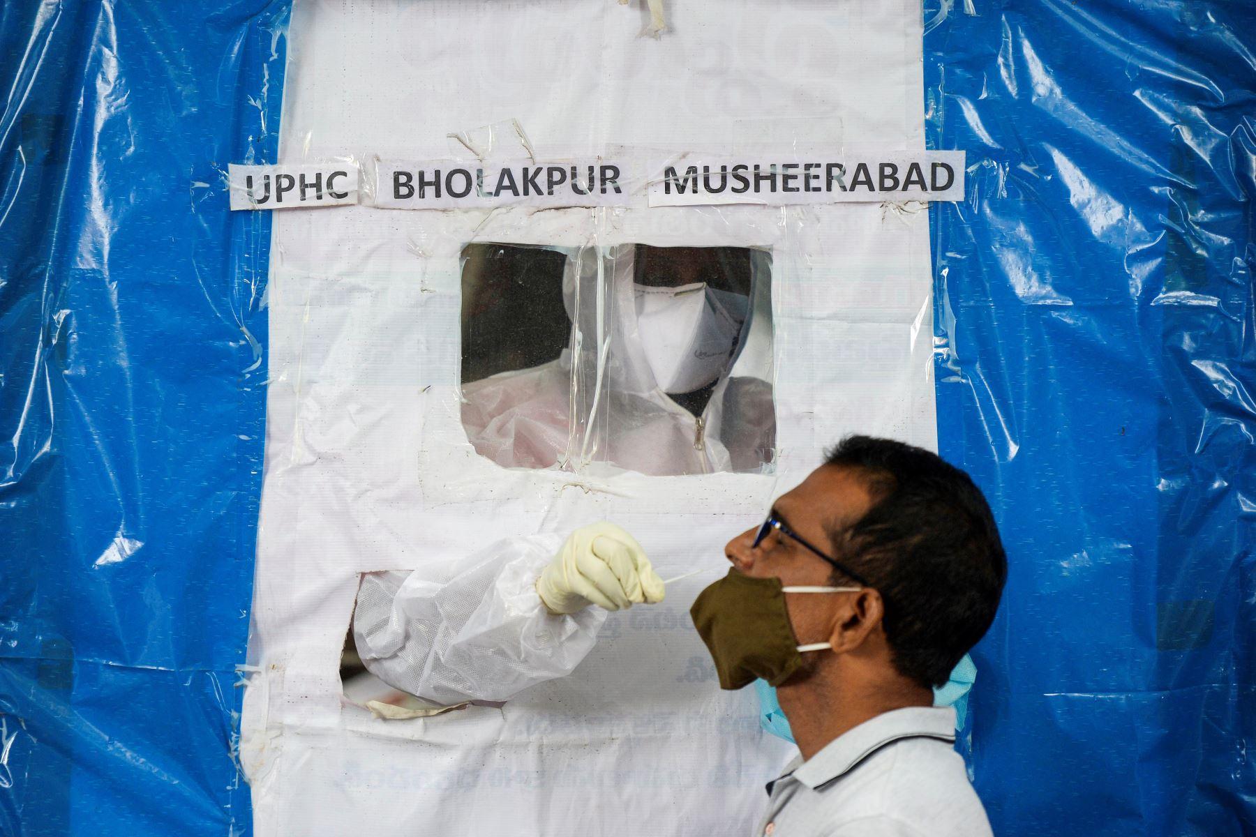 Un trabajador de la salud toma un hisopo de un residente en una caseta de pruebas de covid -19 gratuita improvisada en Hyderabad. Foto: AFP
