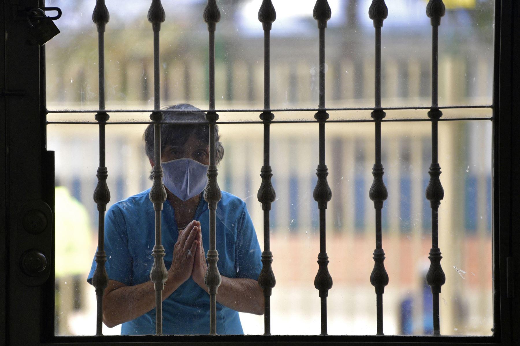 Un feligrés reza frente a la Catedral Parroquial Jesucristo Nuestra Paz durante la romería de la figura del