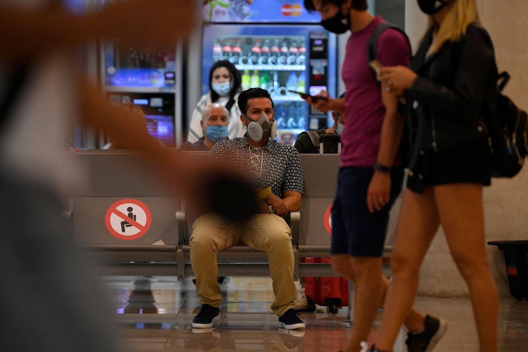Un hombre con mascarilla espera su vuelo en el aeropuerto de El Prat en Barcelona . Foto: AFP