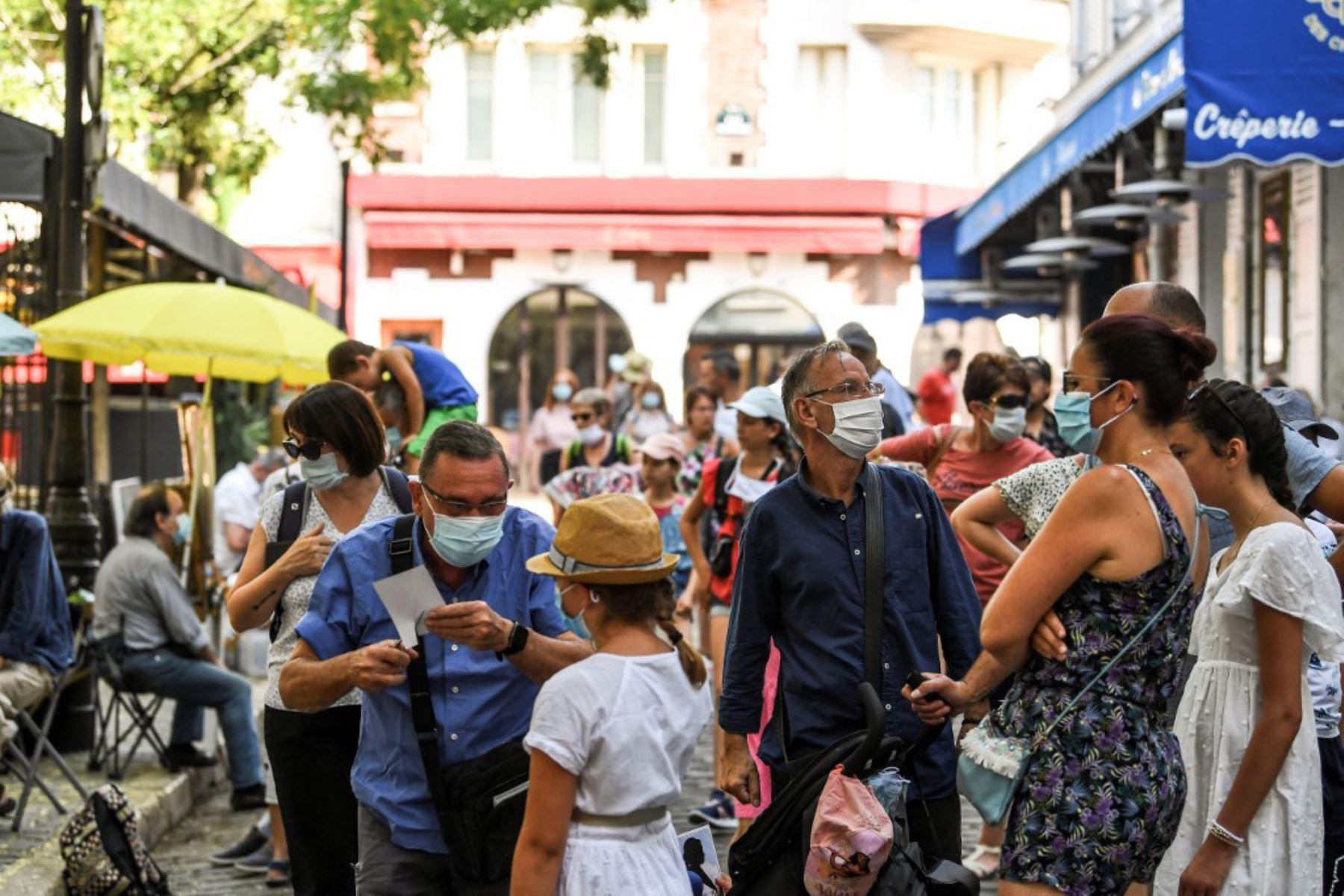 Personas usando mascarillas protectoras visitan el barrio de Montmartre, en París. El alcalde decidió hacer obligatoria la mascarilla en determinadas zonas de la ciudad para luchar contra el aumento de nuevos casos infectados de covid-19   Foto: AFP