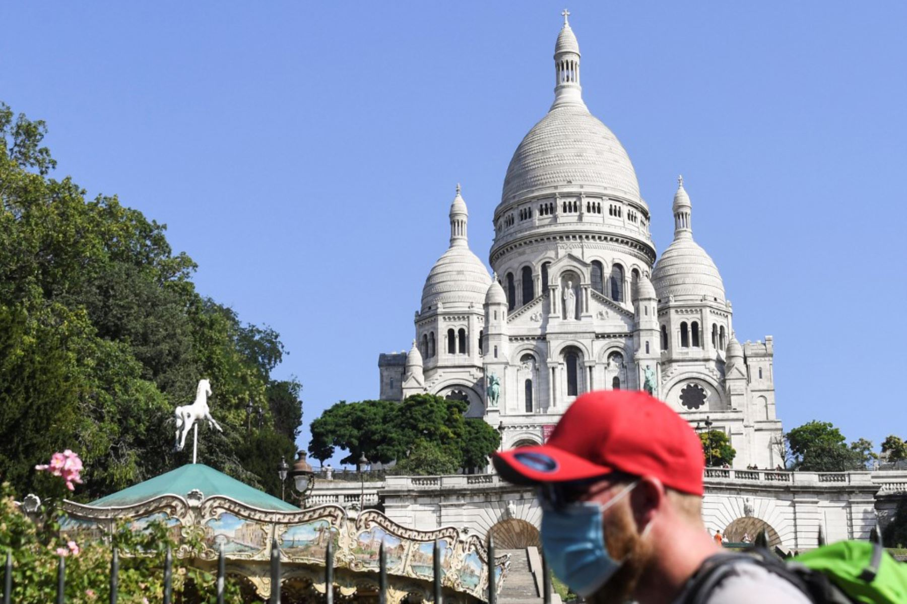 Un hombre con mascarilla protectora pasa por delante de la basílica del Sacre Coeur, en el barrio de Montmartre. Ell alcalde decidió hacer obligatoria la mascarilla en determinadas zonas de la ciudad para luchar contra el surgimiento de nuevos casos de infectados.  Foto: AFP