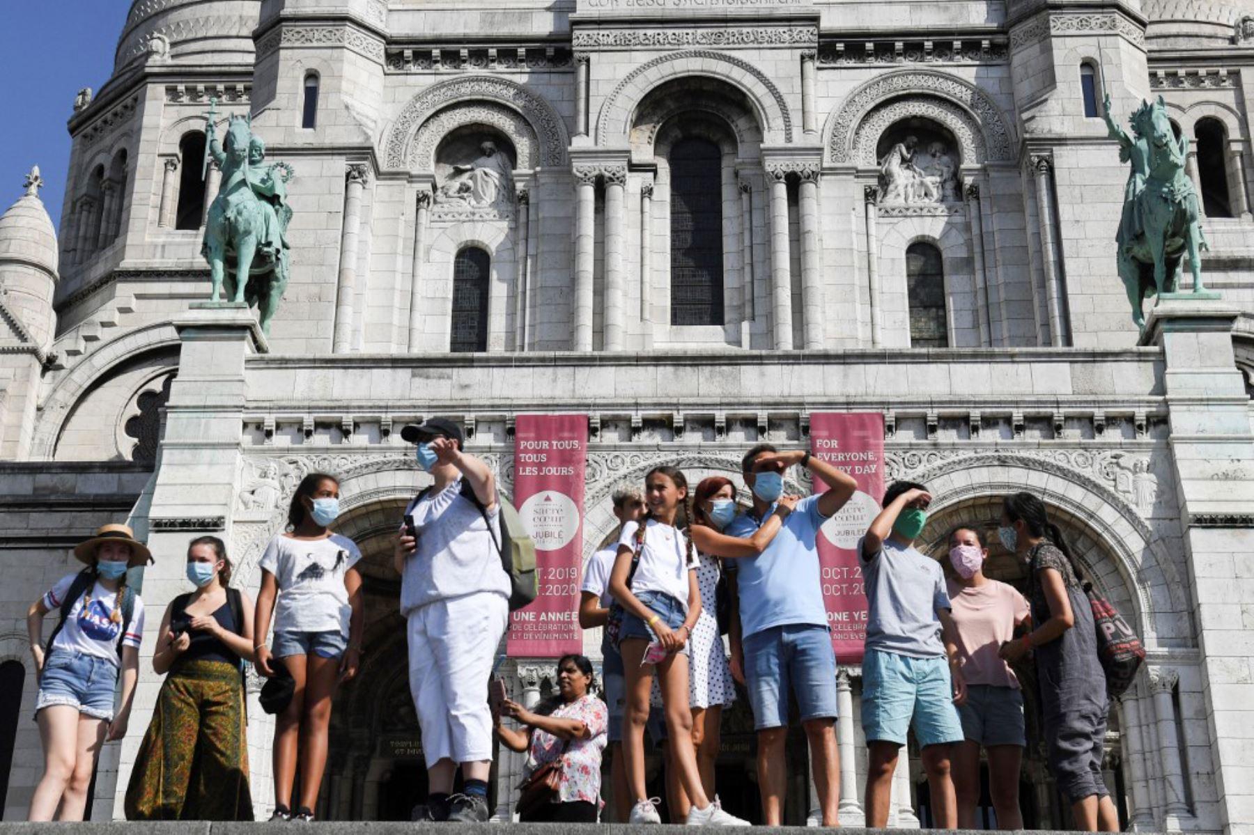 Personas con mascarillas protectoras pasan por delante de la basílica del Sacre Coeur, en el barrio de Montmartre. El alcalde decidió hacer obligatoria la mascarilla en determinadas zonas de la ciudad para luchar contra el surgimiento de nuevos casos de infectados.  Foto: AFP