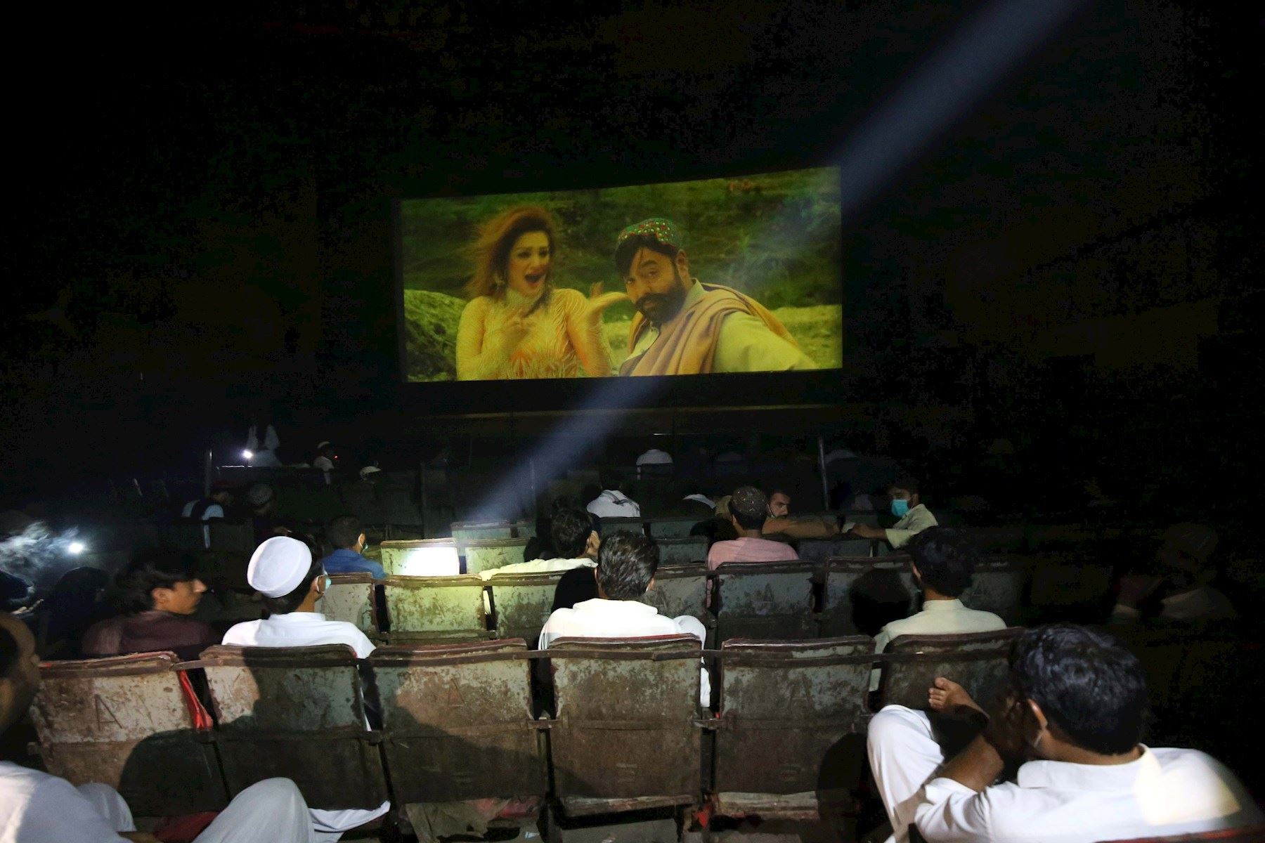 Gente viendo una película en el cine después de que el gobierno levantara la mayoría de las restricciones de coronavirus restantes en el país, en Peshawar, Pakistán.  Foto: EFE
