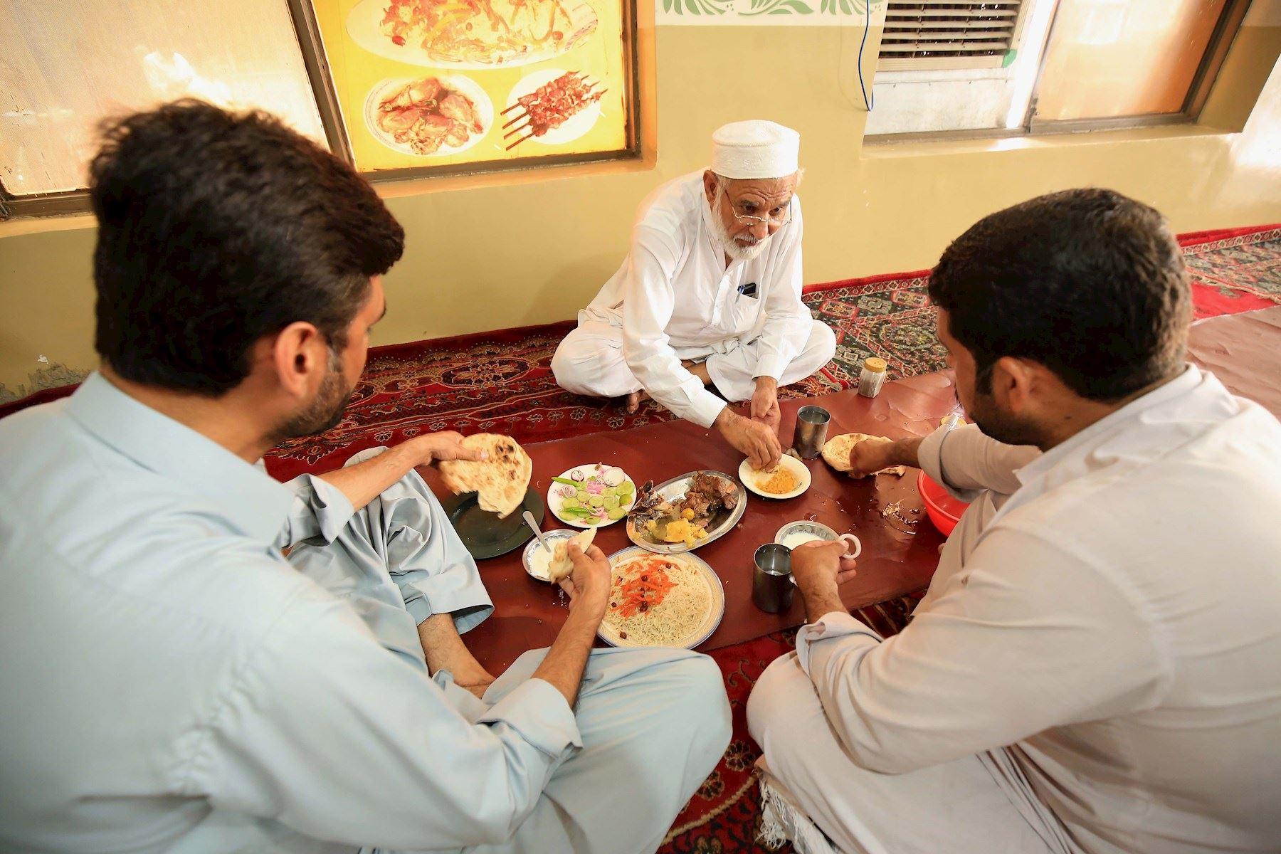 Personas sin mascarillas comparten alimentos después de que el gobierno levantara la mayoría de las restricciones de coronavirus restantes en el país, en Peshawar, Pakistán.  Foto: EFE