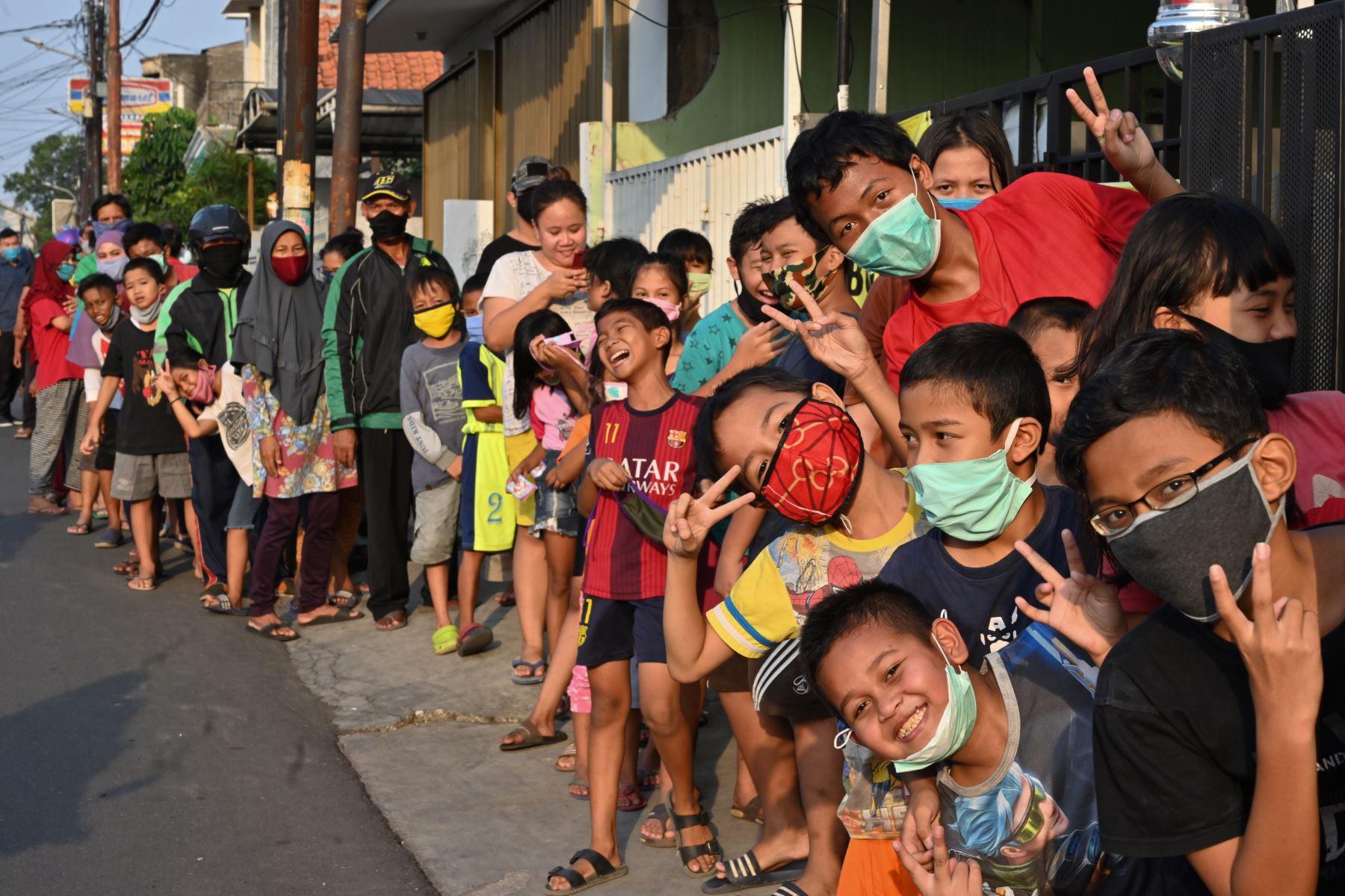 Musulmanes indonesios reaccionan a la fotografía mientras hacen cola para recibir comida gratis y romper su ayuno durante el mes sagrado del Ramadán en Yakarta, Indonesia. Foto: AFP