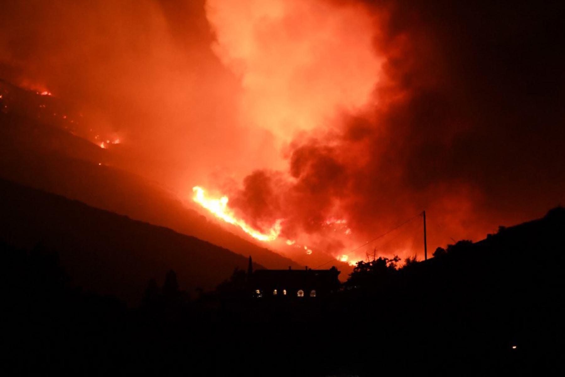 Se ve una casa en la ladera de una colina mientras las llamas del lago Fire arden peligrosamente cerca, en el Bosque Nacional Ángeles. Foto: AFP