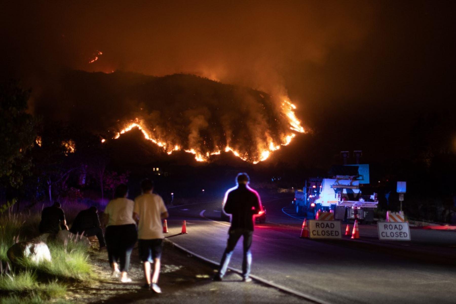 La gente observa el humo y las llamas que se elevan desde el incendio del rancho en las montañas de San Gabriel sobre Azusa, a 25 millas al este de Los Ángeles, California. Foto: AFP