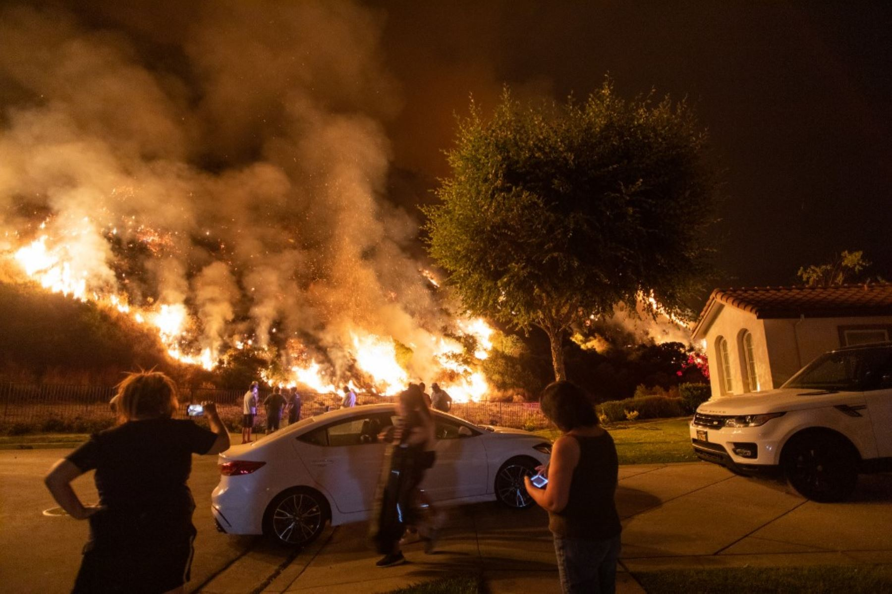 La gente se para junto a las llamas que se elevan desde el incendio del rancho en las montañas de San Gabriel sobre Azusa, a 25 millas al este de Los Ángeles, California. Foto: AFP