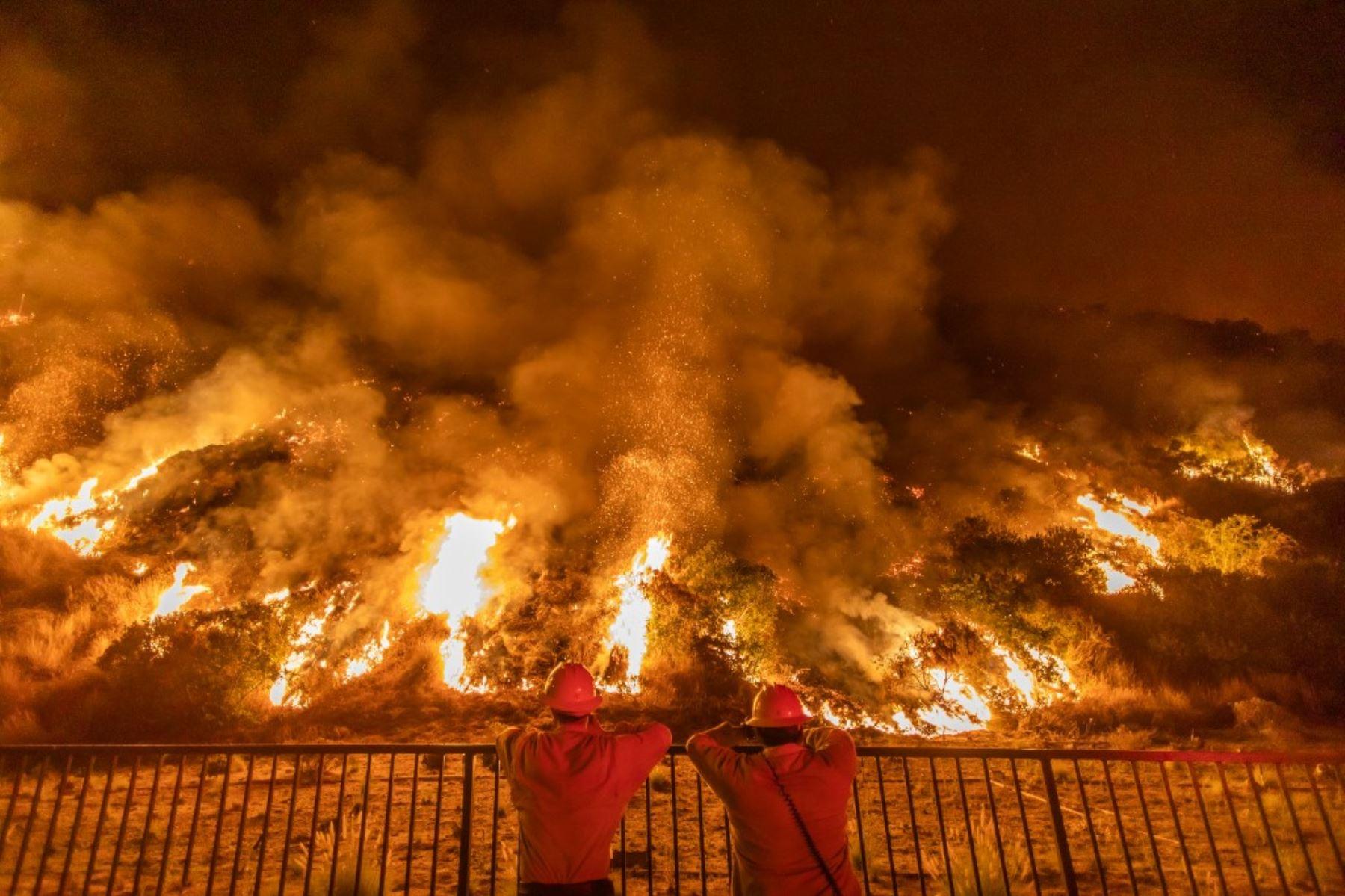 Los bomberos observan el humo y las llamas que se elevan desde las montañas de San Gabriel sobre Azusa, a 25 millas al este de Los Ángeles, California. Foto: AFP
