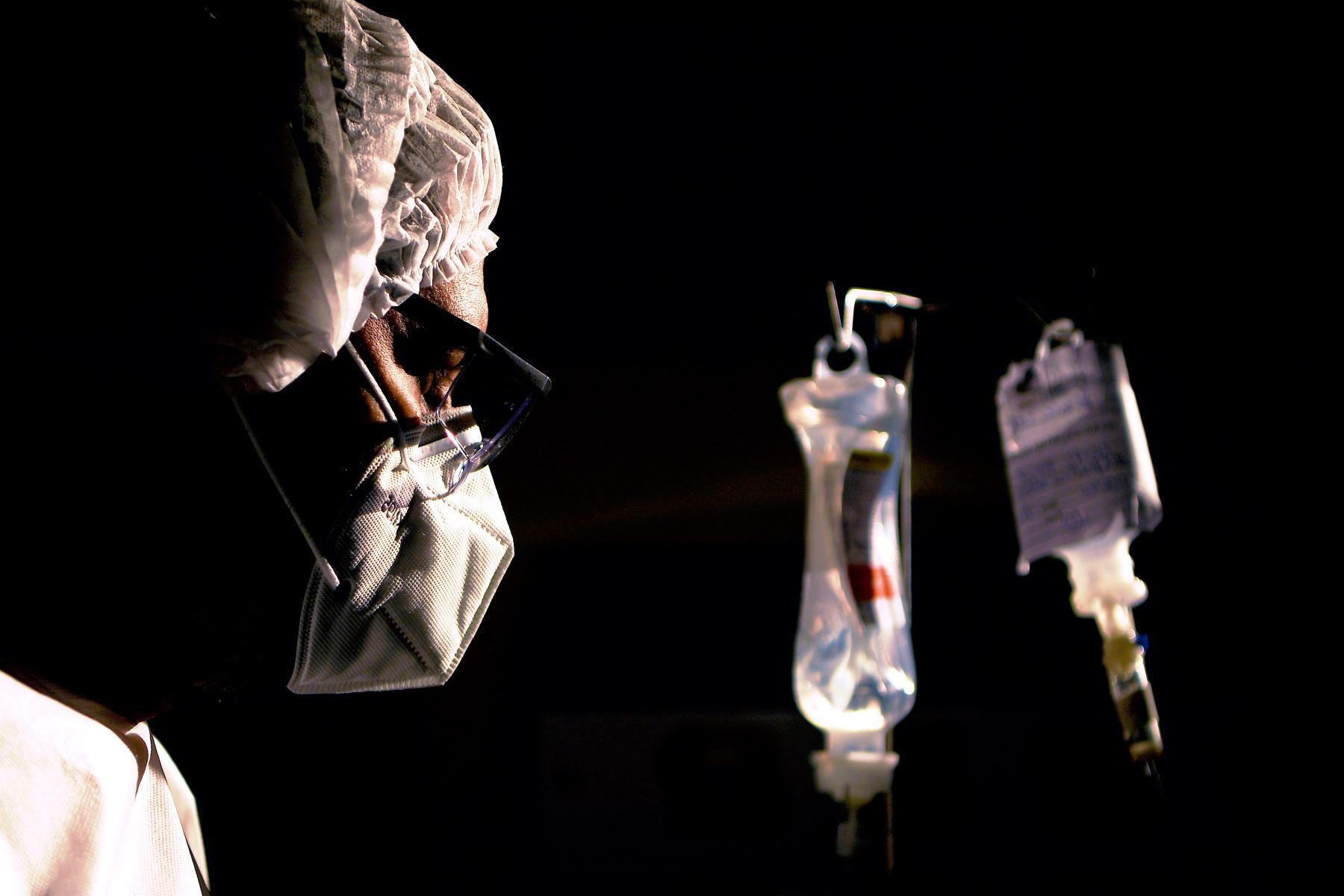 En esta foto de archivo tomada el 22 de junio de 2020, un cirujano revisa el goteo intravenoso de uno de sus pacientes con covid-19, en el hospital Oceánico en Niteroi, Río de Janeiro, Brasil, durante la pandemia de coronavirus. Foto: AFP