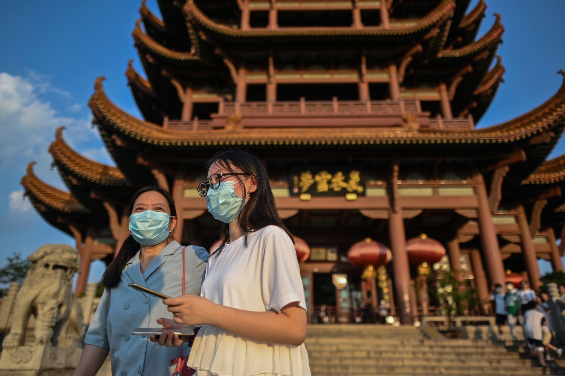 Turistas con máscaras faciales visitan la Torre de la Grulla Amarilla en Wuhan, provincia central de Hubei en China. Foto: AFP