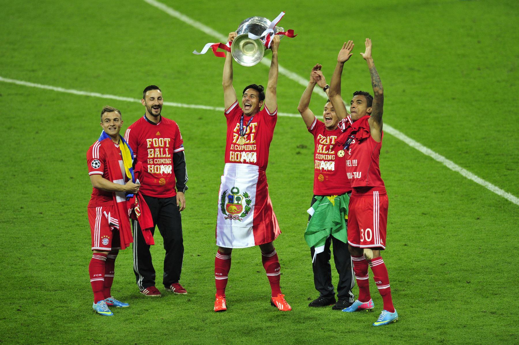 El delantero peruano del Bayern Munich, Claudio Pizarro, celebra con el trofeo en el campo junto a sus compañeros de equipo después de su victoria en la final de la UEFA Champions League entre el Borussia Dortmund y el Bayern Munich, en el estadio de Wembley en Londres, el 25 de mayo de 2013. Foto: AFP