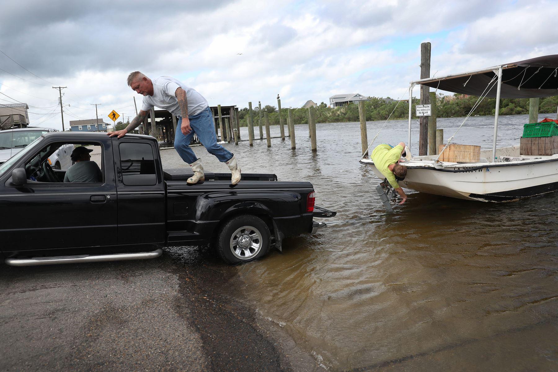Dos personas intentan sacar su bote del agua antes de la posible llegada del huracán Sally en Shell Beach, Louisiana. Foto: AFP
