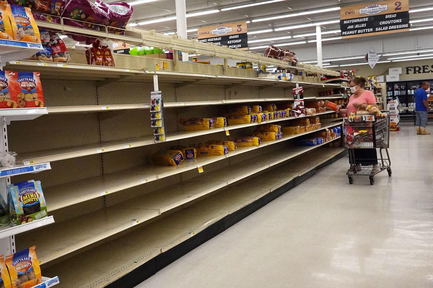 Un comprador busca pan en un estante parcialmente vacío mientras la gente se prepara antes de la posible llegada del huracán Sally, en Bayou La Batre, Alabama. Foto: AFP