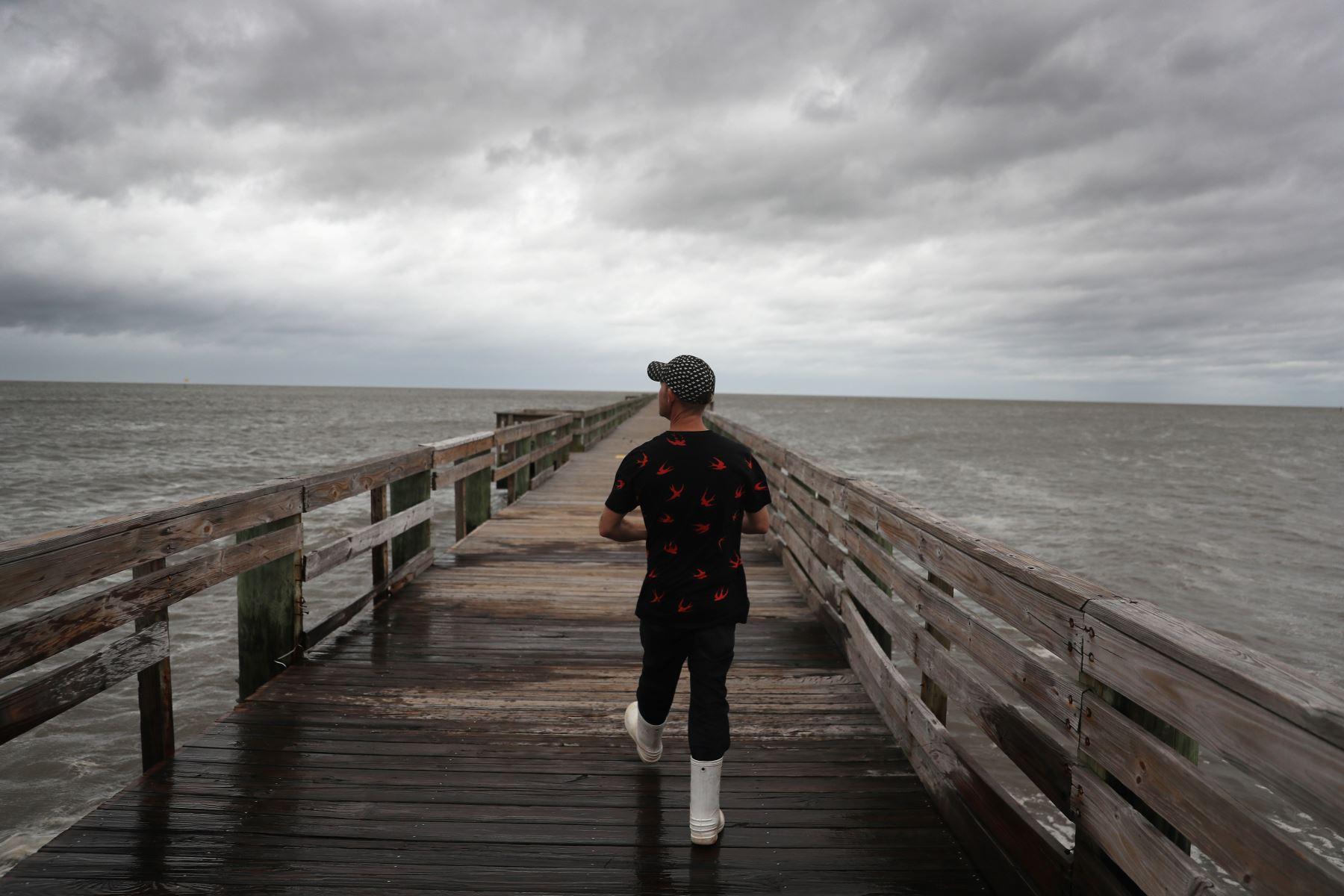 Un joven camina a lo largo de un muelle para encontrar un lugar para pescar antes de la posible llegada del huracán Sally, en Biloxi, Mississippi. Foto: AFP