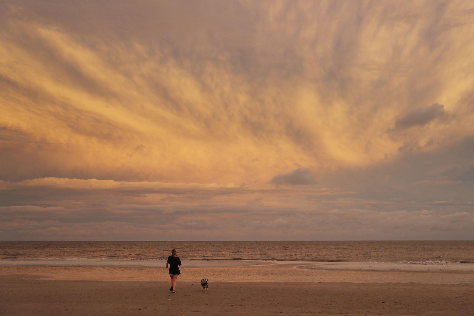 Una joven disfruta de la playa junto a su perro, antes de la llegada del huracán Sally, en Mississippi. Foto: AFP