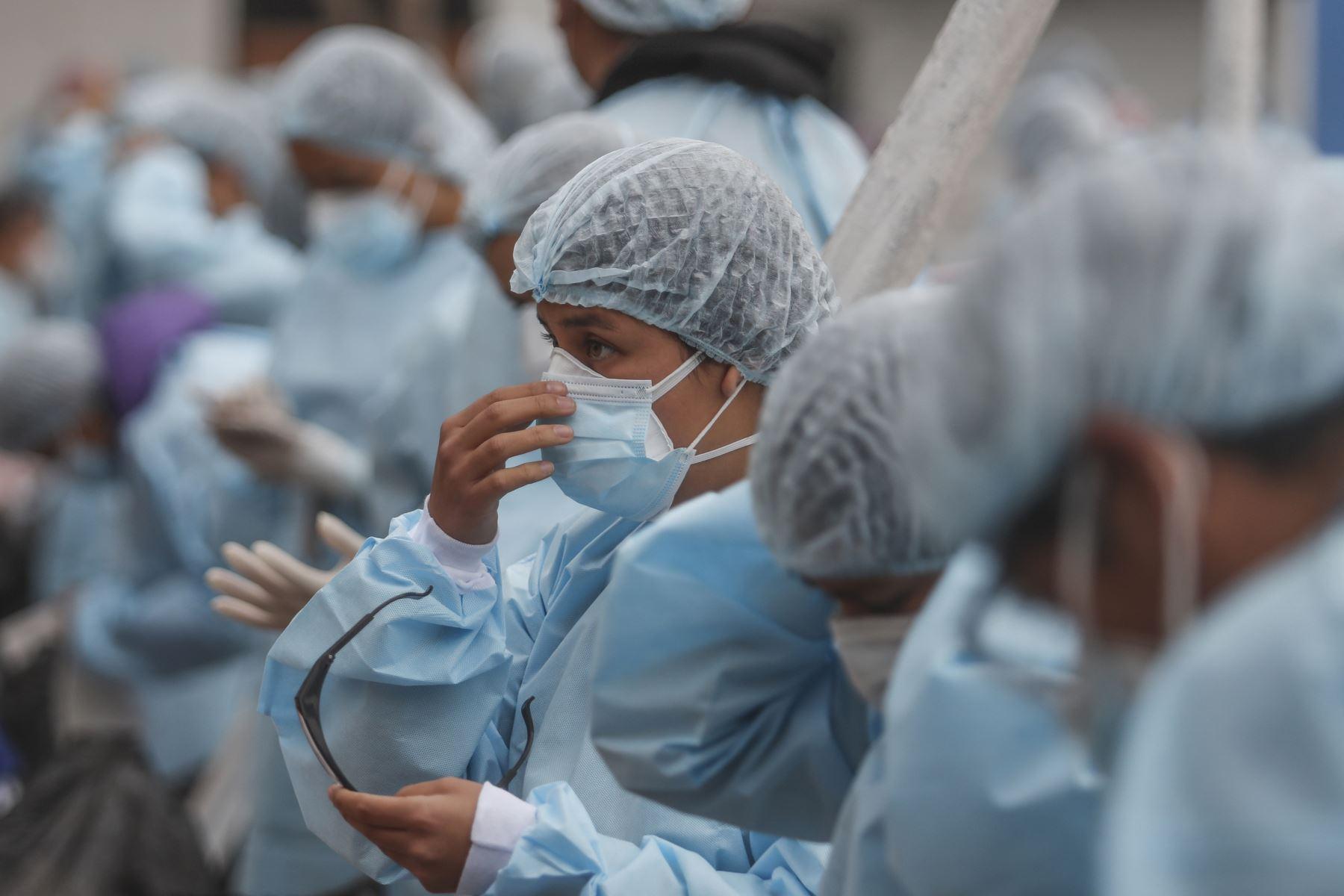 Las brigadas de salud se colocan sus implementos de bioseguridad en una losa deportiva del AA.HH. Pampa Los Olivares-Villa Leticia, en Cajamarquilla. Foto: ANDINA/Renato Pajuelo