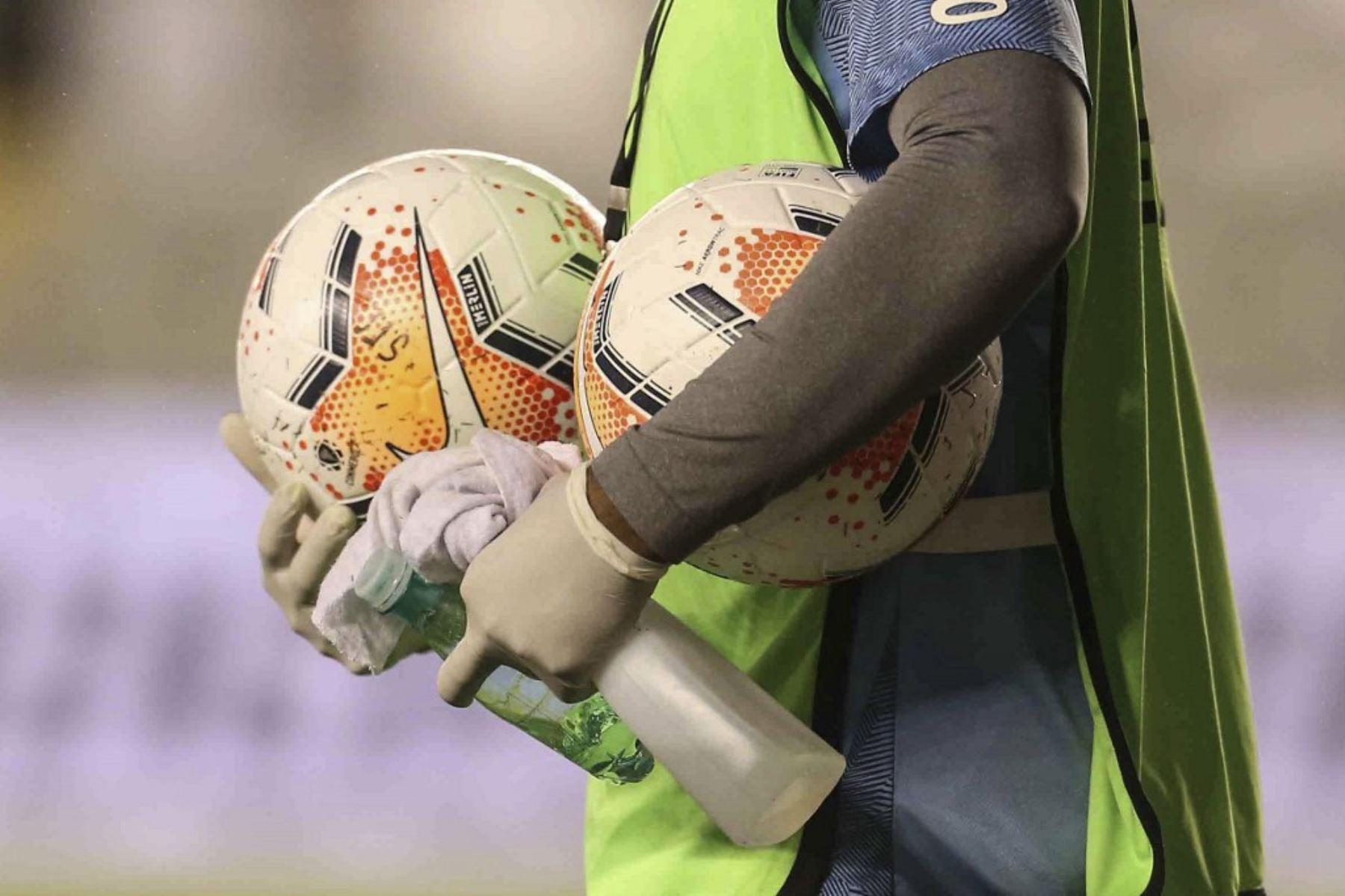 Un recogepelotas sostiene balones y desinfectante durante un partido de fútbol a puertas cerradas por la fase de grupos de la Copa Libertadores entre el Santos de Brasil y el Olimpia de Paraguay, en el estadio Vila Belmiro en Santos. Foto: AFP