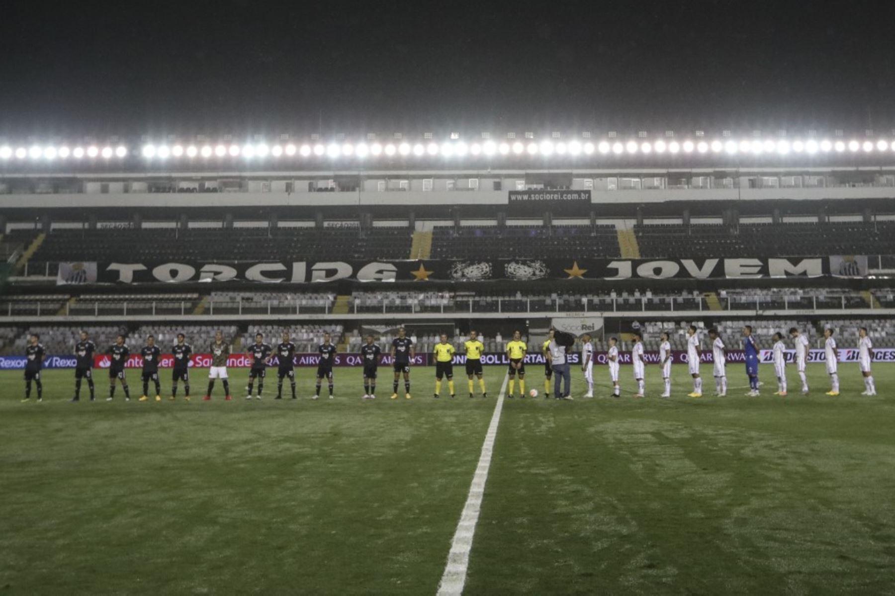 Los jugadores se forman en el campo antes de un partido de fútbol a puertas cerradas por la fase de grupos de la Copa Libertadores entre el Santos de Brasil y el Olimpia de Paraguay, en el estadio Vila Belmiro en Santos. Foto: AFP