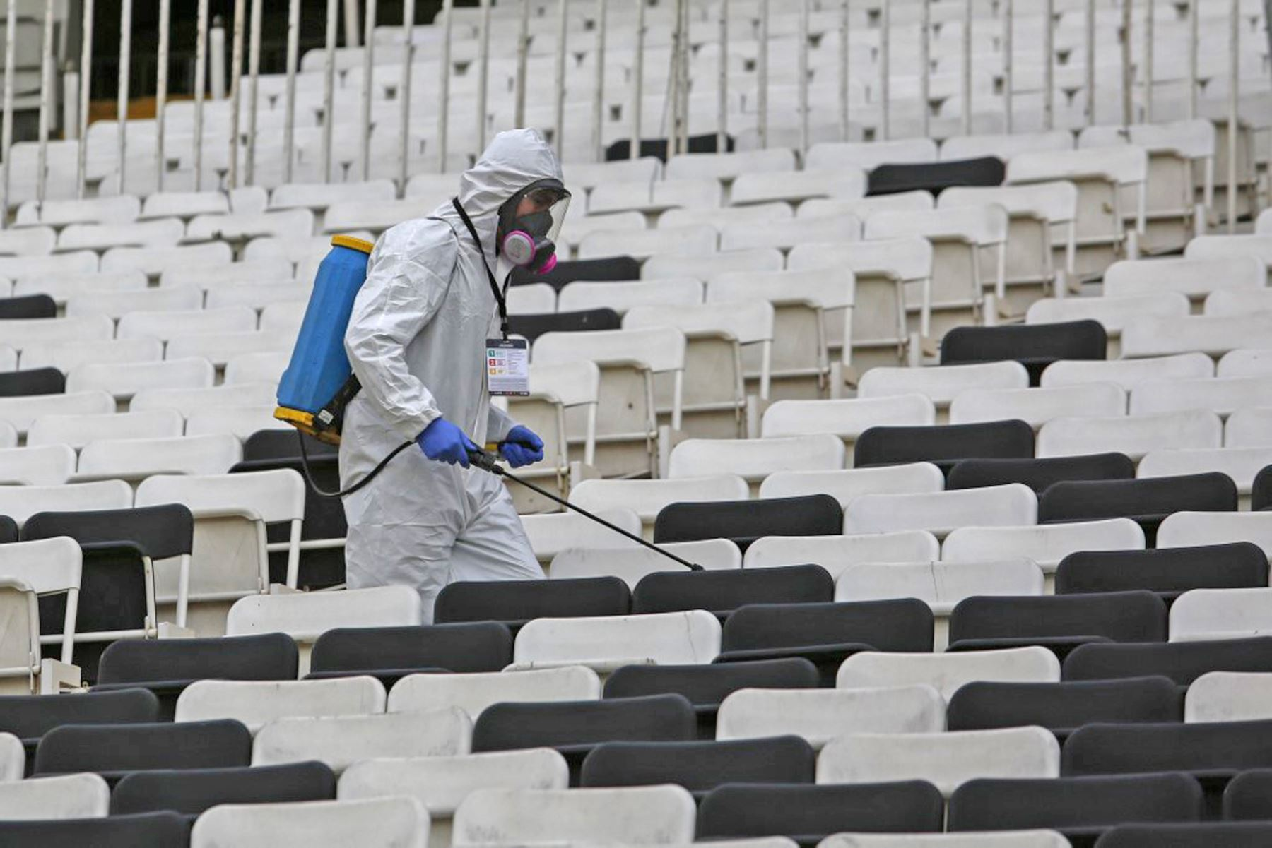 Un trabajador desinfecta los asientos antes del inicio del partido de fútbol a puerta cerrada de la fase de grupos de la Copa Libertadores entre Colo Colo de Chile y Peñarol de Uruguay, en el estadio Monumental de Santiago. Foto: AFP