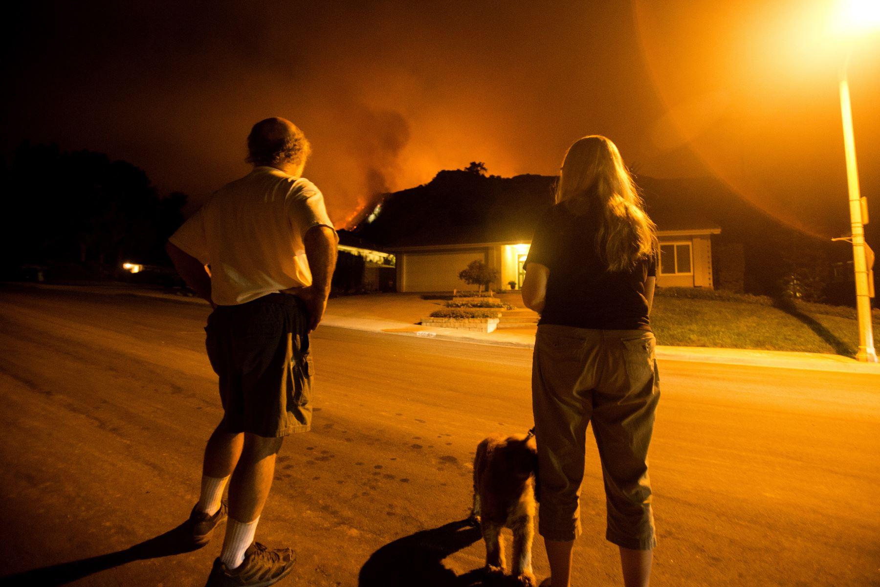Las personas observan cómo arden las llamas en las laderas detrás de sus viviendas en Monrovia, California. Foto: AFP