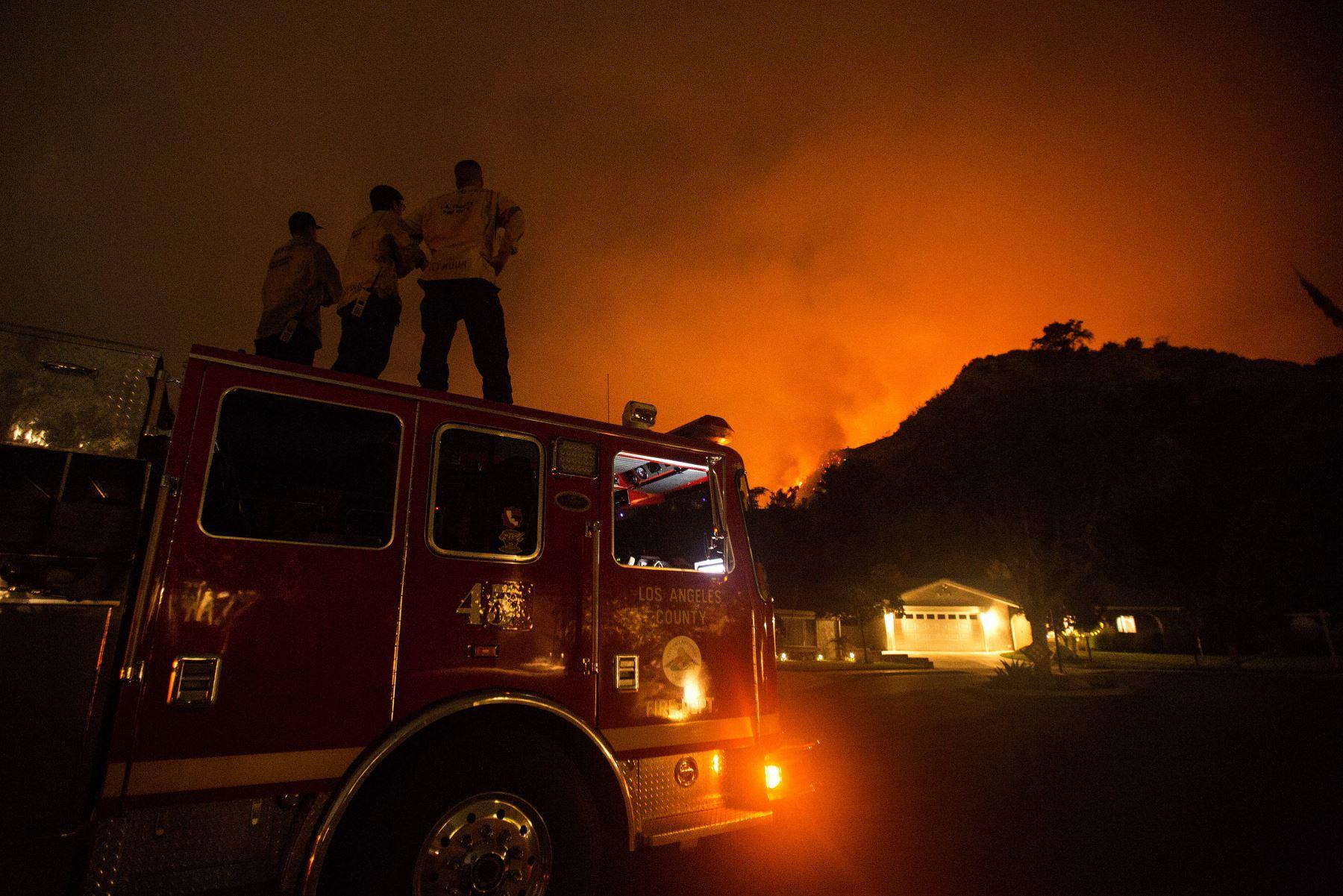 Los bomberos observan cómo arden las laderas detrás de las casas en Monrovia, California. Foto: AFP