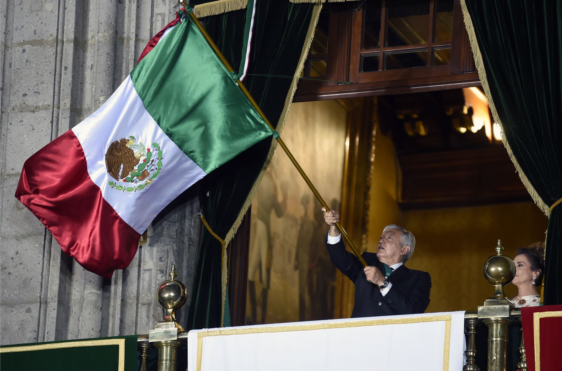 """El presidente de México, Andrés Manuel López Obrador, ondea una bandera mexicana, flanqueada por su esposa Beatriz Gutiérrez, en el balcón principal del Palacio Nacional durante la ceremonia """"El Grito"""" (El Grito) que marca el inicio de las celebraciones del Día de la Independencia en la Ciudad de México. Foto: AFP"""