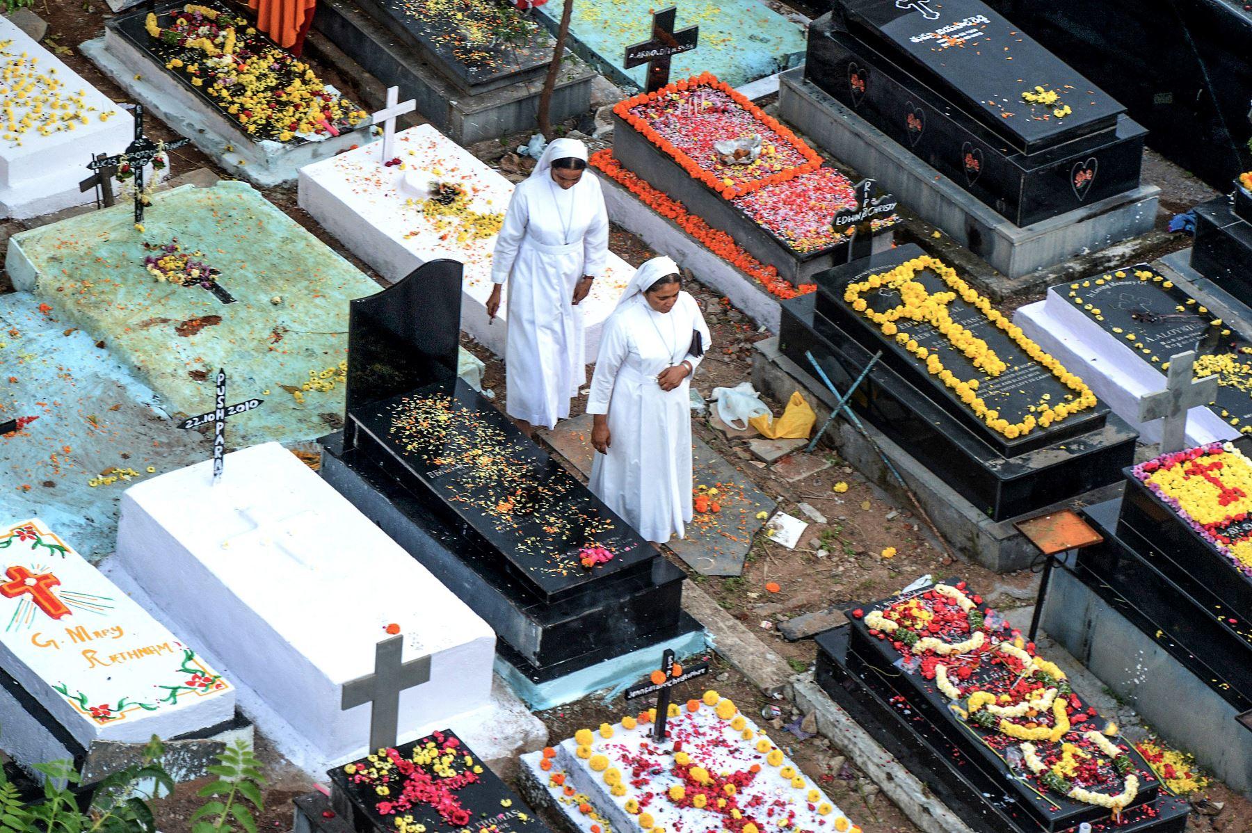 Monjas católicas caminan entre las tumbas para ofrecer oraciones a las hermanas fallecidas durante el Día de los Difuntos en un cementerio en Hyderabad en la India. Foto: AFP