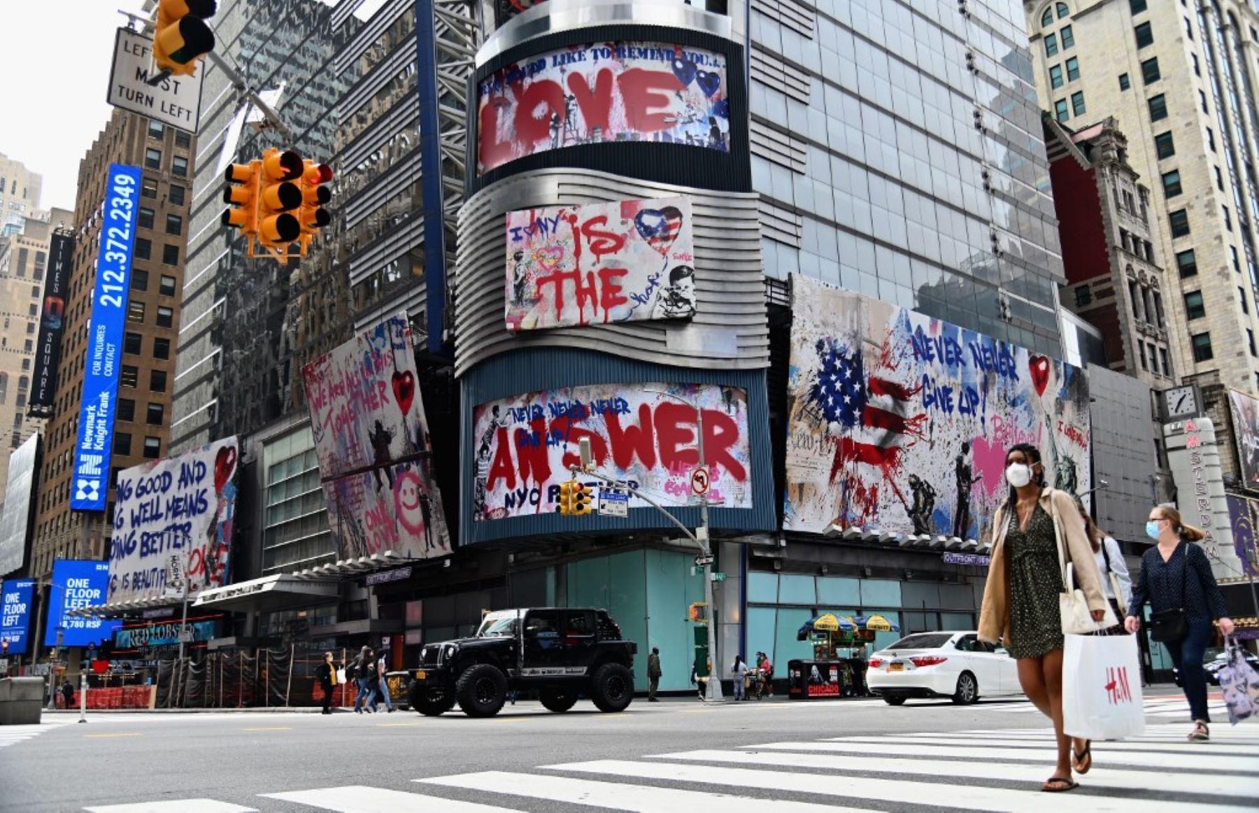 Poca gente pasa junto a una valla publicitaria cerca de Times Square en la ciudad de Nueva York, debido al covid-19.Foto:AFP