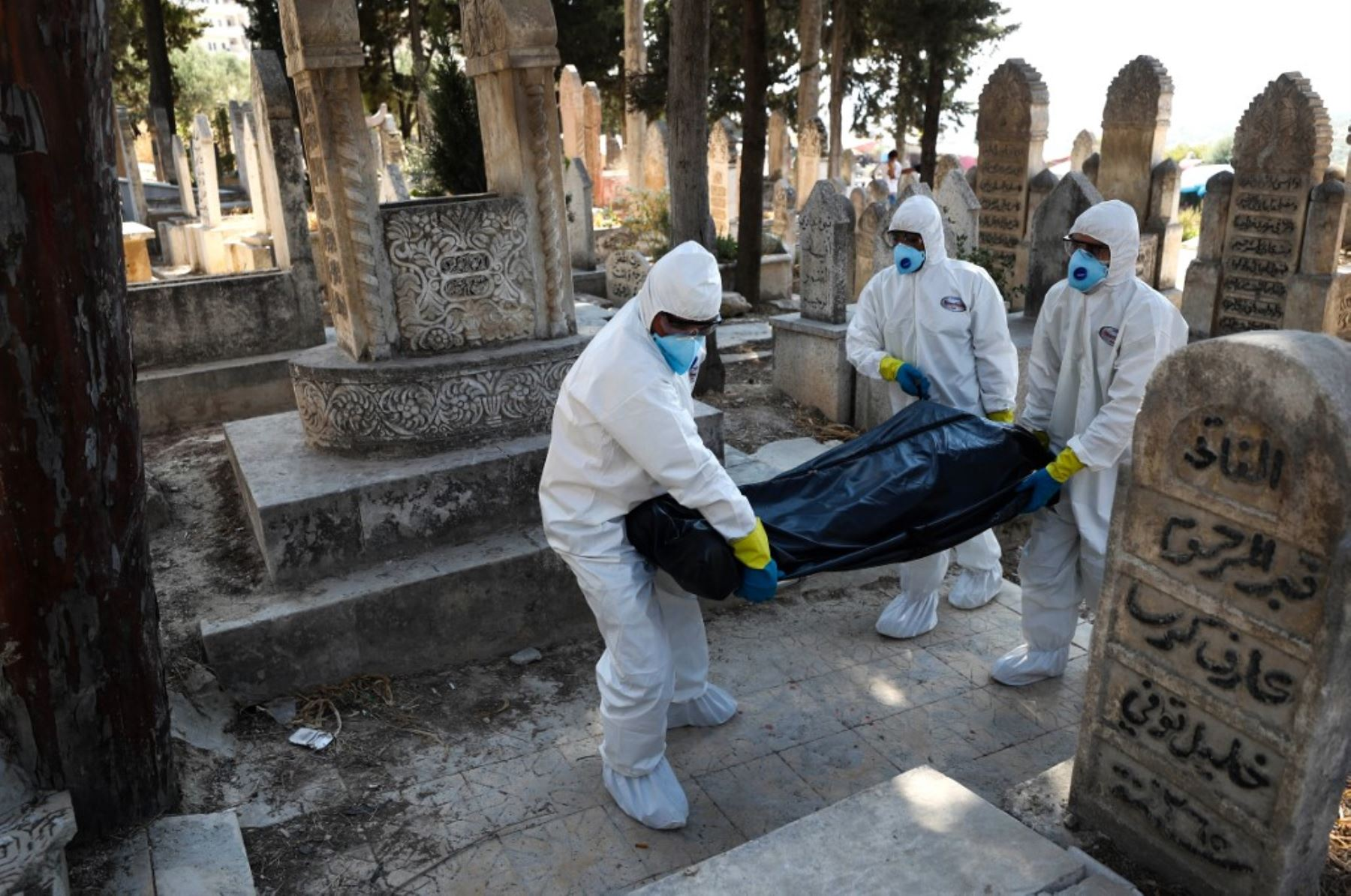 Trabajadores de salud con protectores llevan el cuerpo de un sirio desplazado de 62 años que murió de la enfermedad del covid-19, para ser enterrado en la ciudad de Salqin, en la provincia de Idlib, noroeste de Siria.Foto:AFP