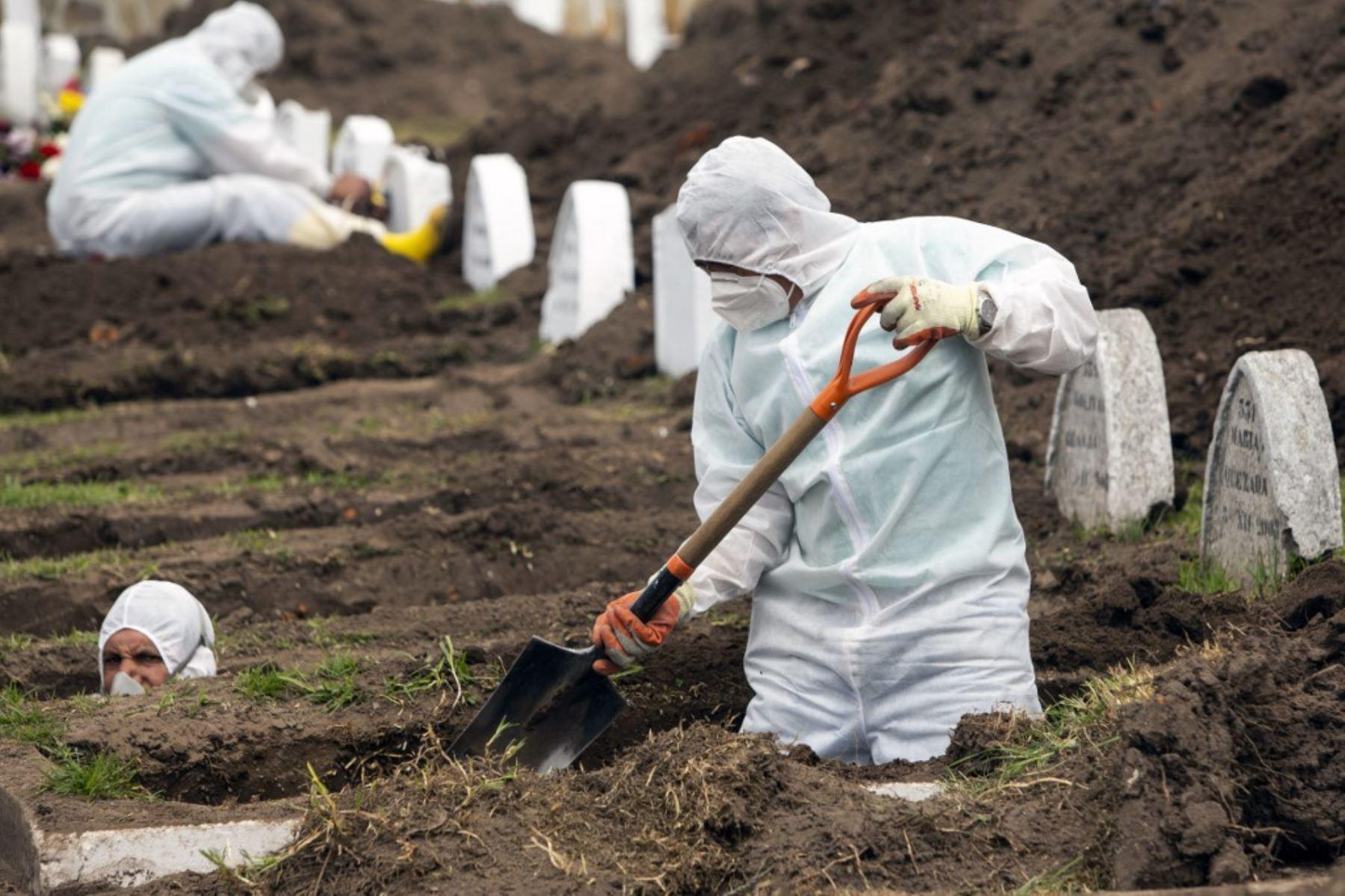 Trabajadores con equipo de bioseguridad preparan tumbas para presuntas víctimas del nuevo coronavirus Covid-19, en el Cementerio de San Diego, en el Centro Colonial de Quito.Foto:AFP