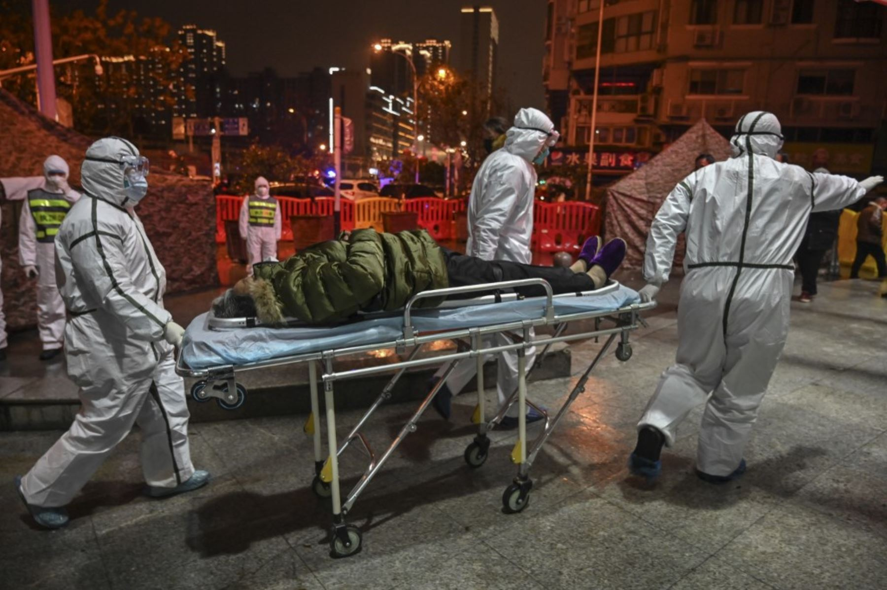 Miembros del personal médico con ropa protectora ayudan a un paciente  con covid-19 y lo  trasladan al Hospital de la Cruz Roja de Wuhan para detener la propagación del coronavirus.Foto:AFP