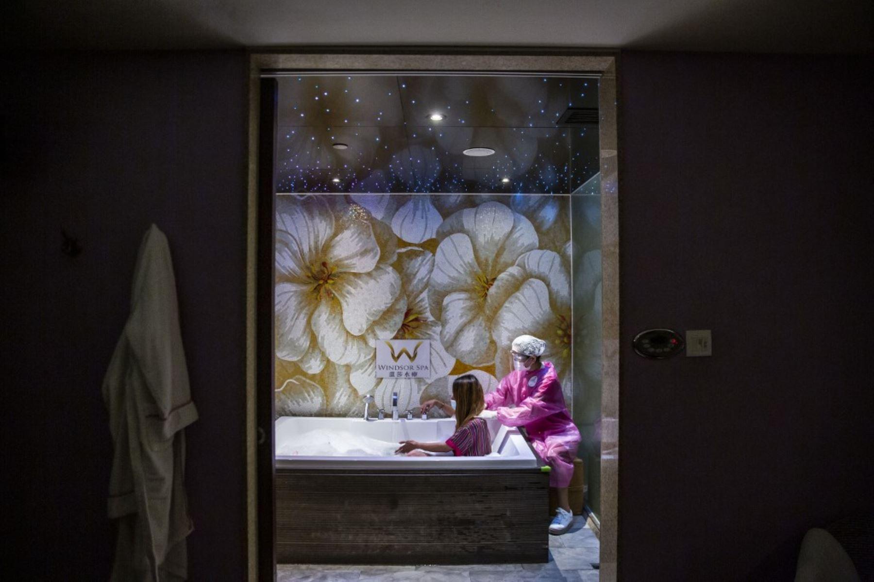 Un empleado que usa una máscara, protector facial y bata le da a un cliente un masaje en un spa en una casa de baños en Hong Kong, donde abrieron bares, piscinas y parques de diversiones, con restricciones después de los cierres debido a la tercera ola del coronavirus covid-19. Foto:AFP