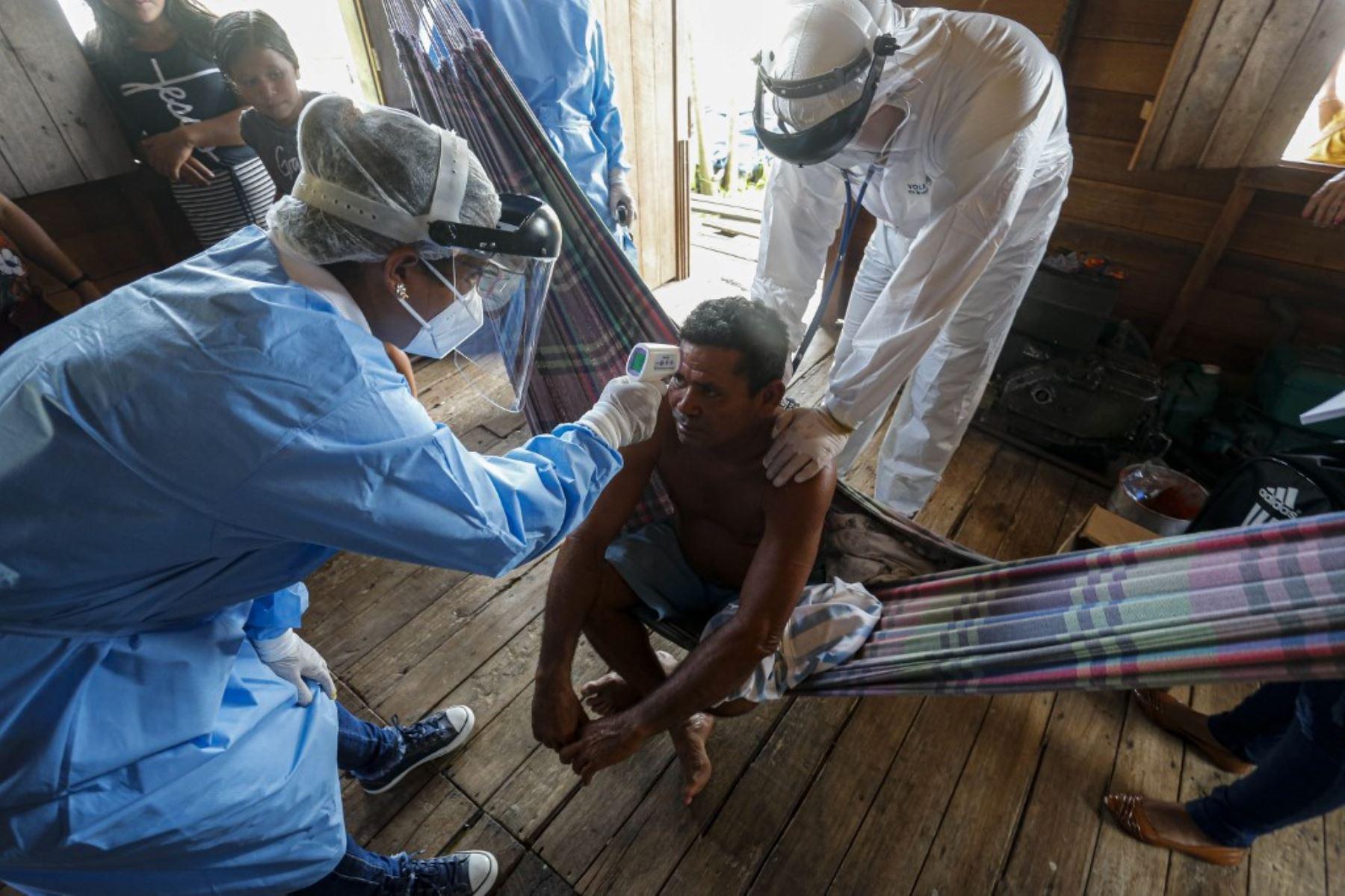 Trabajadores de salud del gobierno controlan la temperatura de un hombre en una comunidad ribereña del río Murutipucu en Igarape-Miri, Baixo Tocantins, en Brasil, para detectar casos de covid-19 entre la población.Foto:AFP