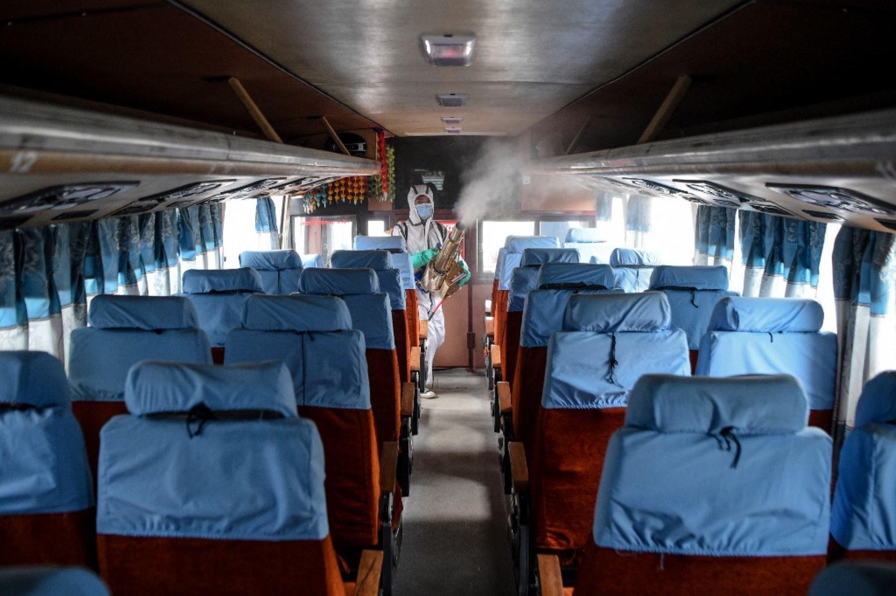 Un trabajador que lleva un equipo de protección personal sigue desinfectando un autobús mientras el gobierno suaviza las restricciones impuestas como medida preventiva contra el coronavirus en el transporte público de larga distancia en Katmandú.Foto:AFP