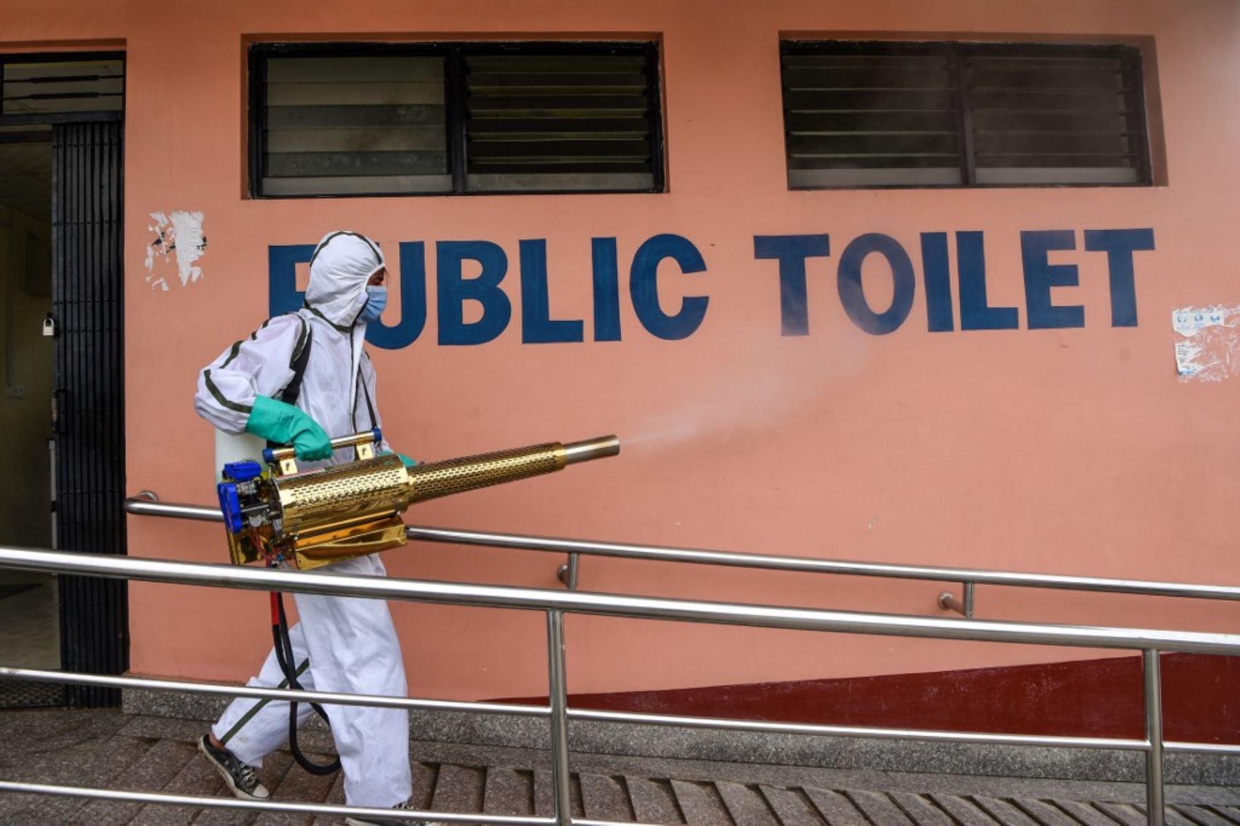 Un trabajador que usa un equipo de protección personal desinfecta los baños públicos en una estación de autobuses mientras el gobierno suaviza las restricciones impuestas como medida preventiva contra el coronavirus Covid-19.Foto:AFP