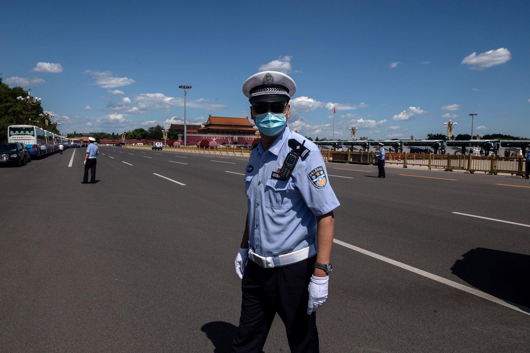 Agentes de policía aseguran una calle fuera del Gran Salón del Pueblo, donde se realizó una ceremonia en honor a las personas que lucharon contra la pandemia del coronavirus, en Beijing. Foto: AFP