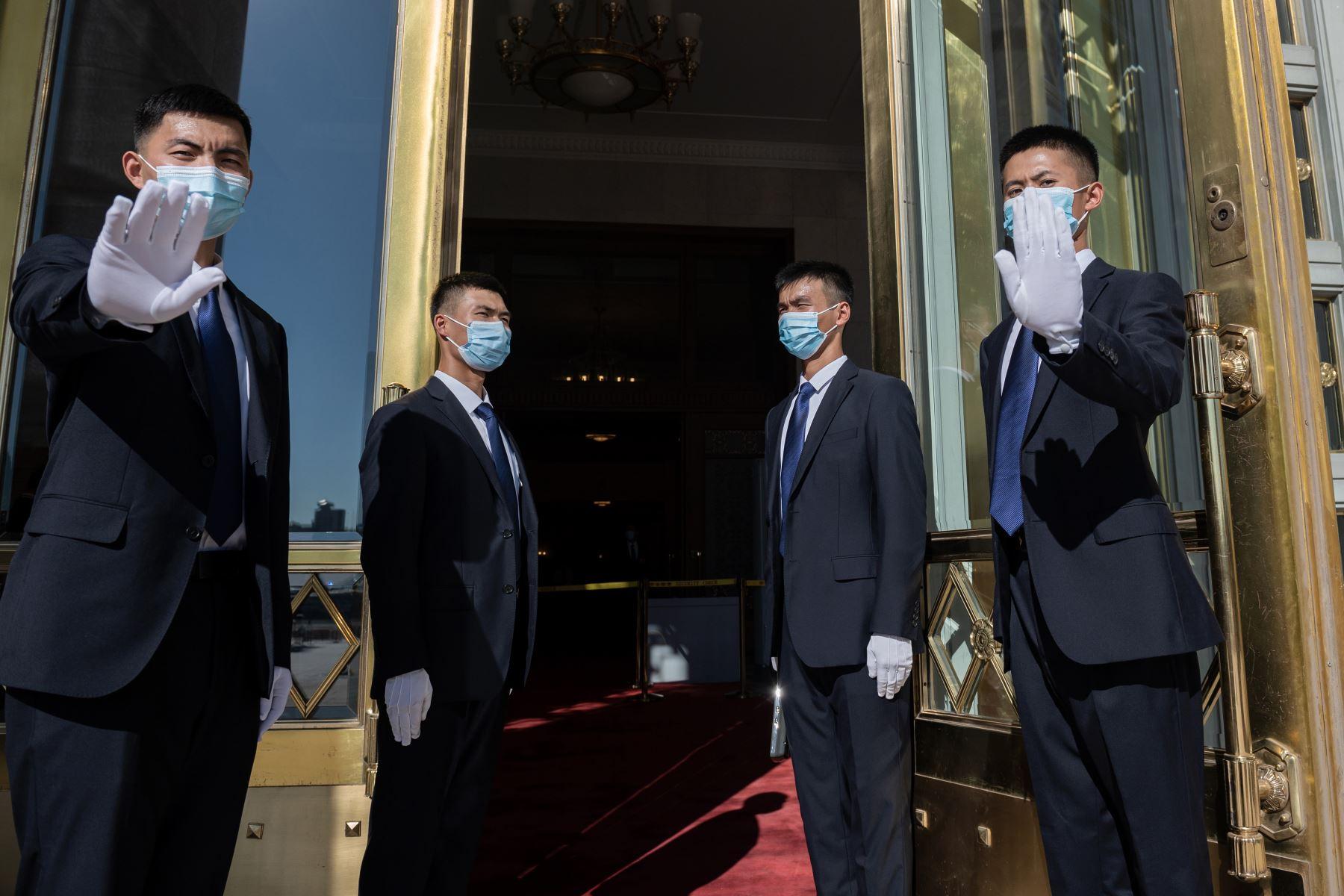 El personal de seguridad se para fuera del Gran Salón del Pueblo, donde realizan una ceremonia en honor a las personas que lucharon contra la pandemia del coronavirus, en Beijing. Foto: AFP