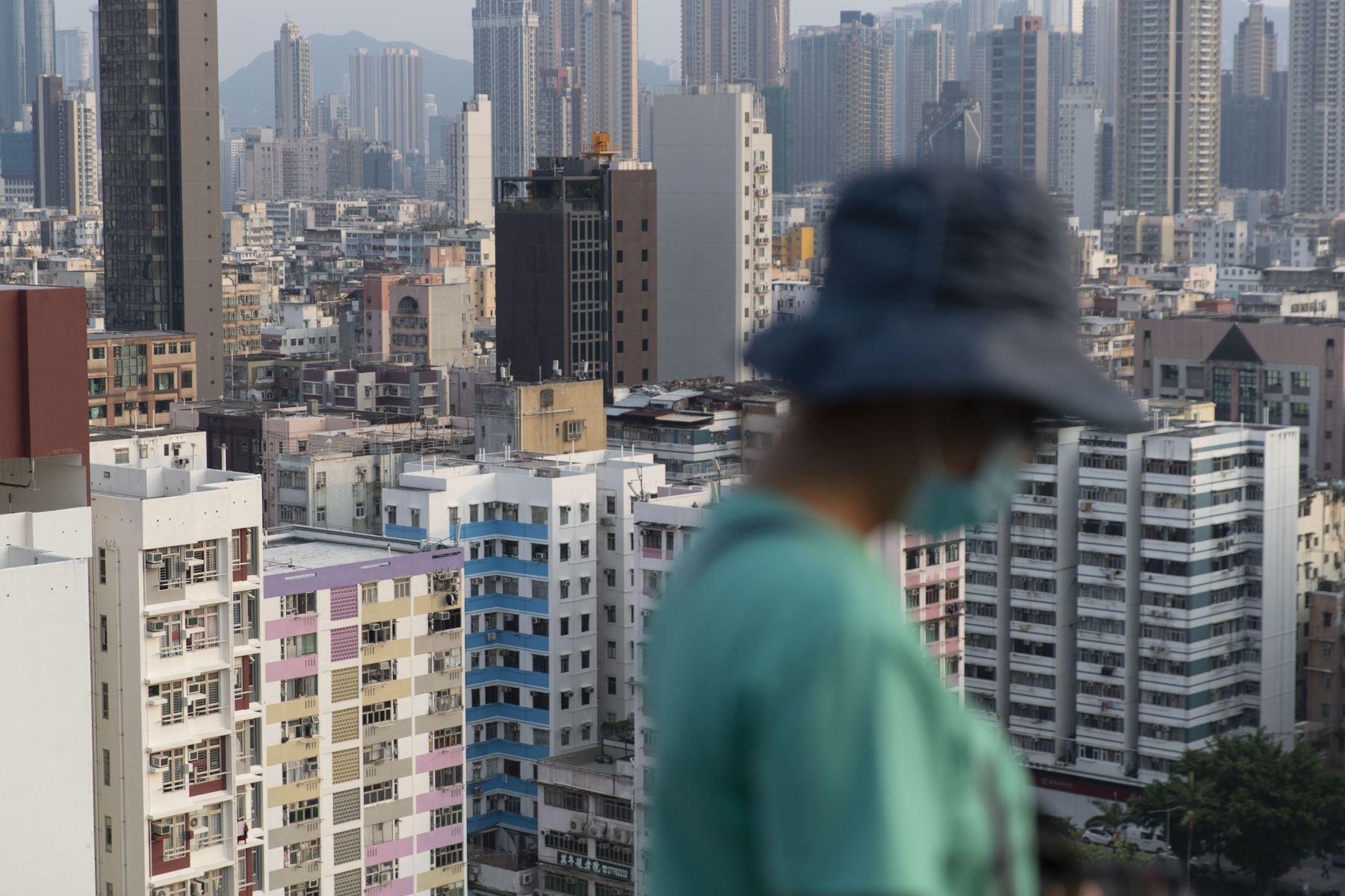 Una mujer usa una mascarilla como medida de precaución ante el coronavirus pasa frente a edificios de viviendas, en Hong Kong. Foto: AFP
