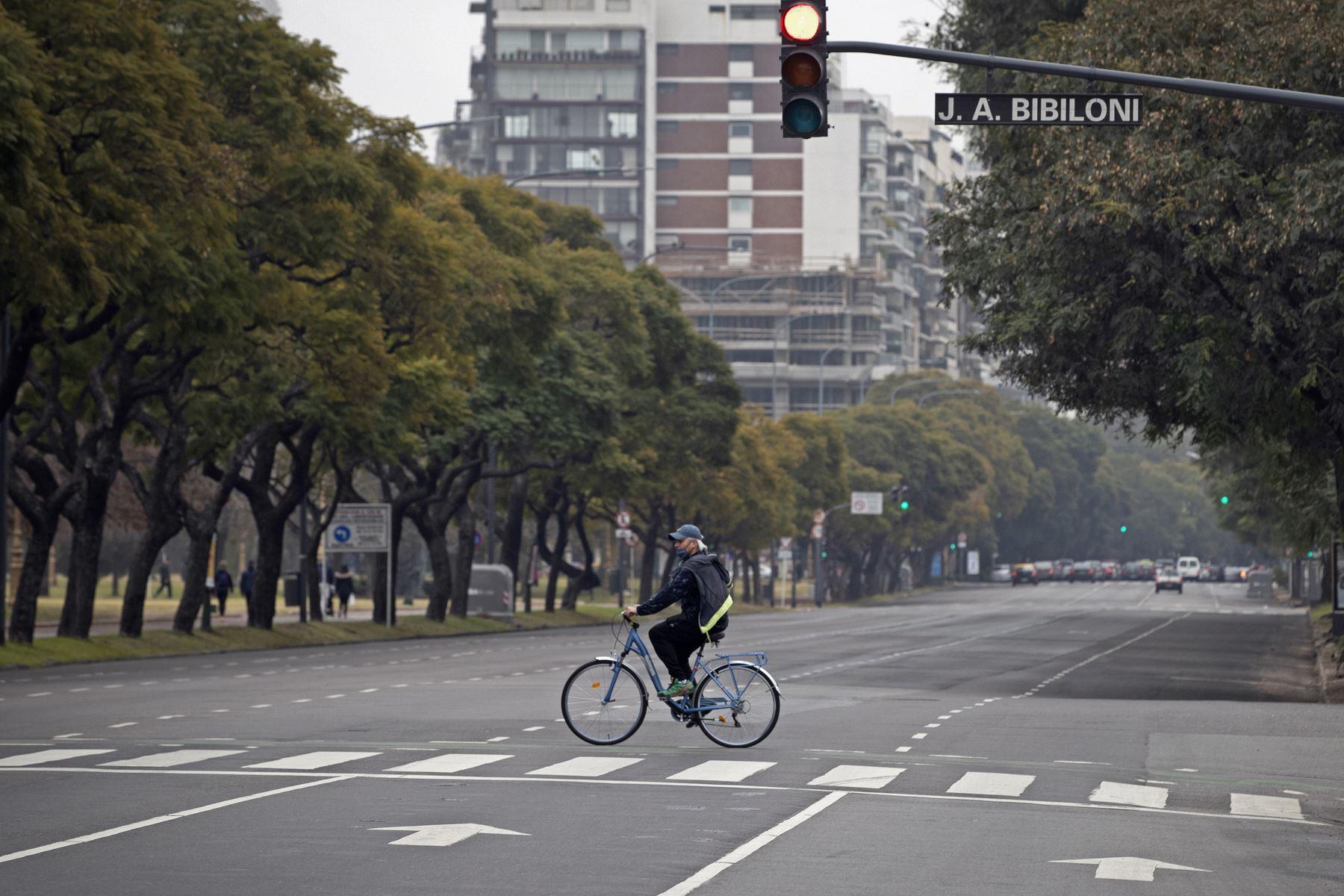 Un hombre cruza una avenida en bicicleta, en el centro de Buenos Aires, Argentina. Foto: AFP