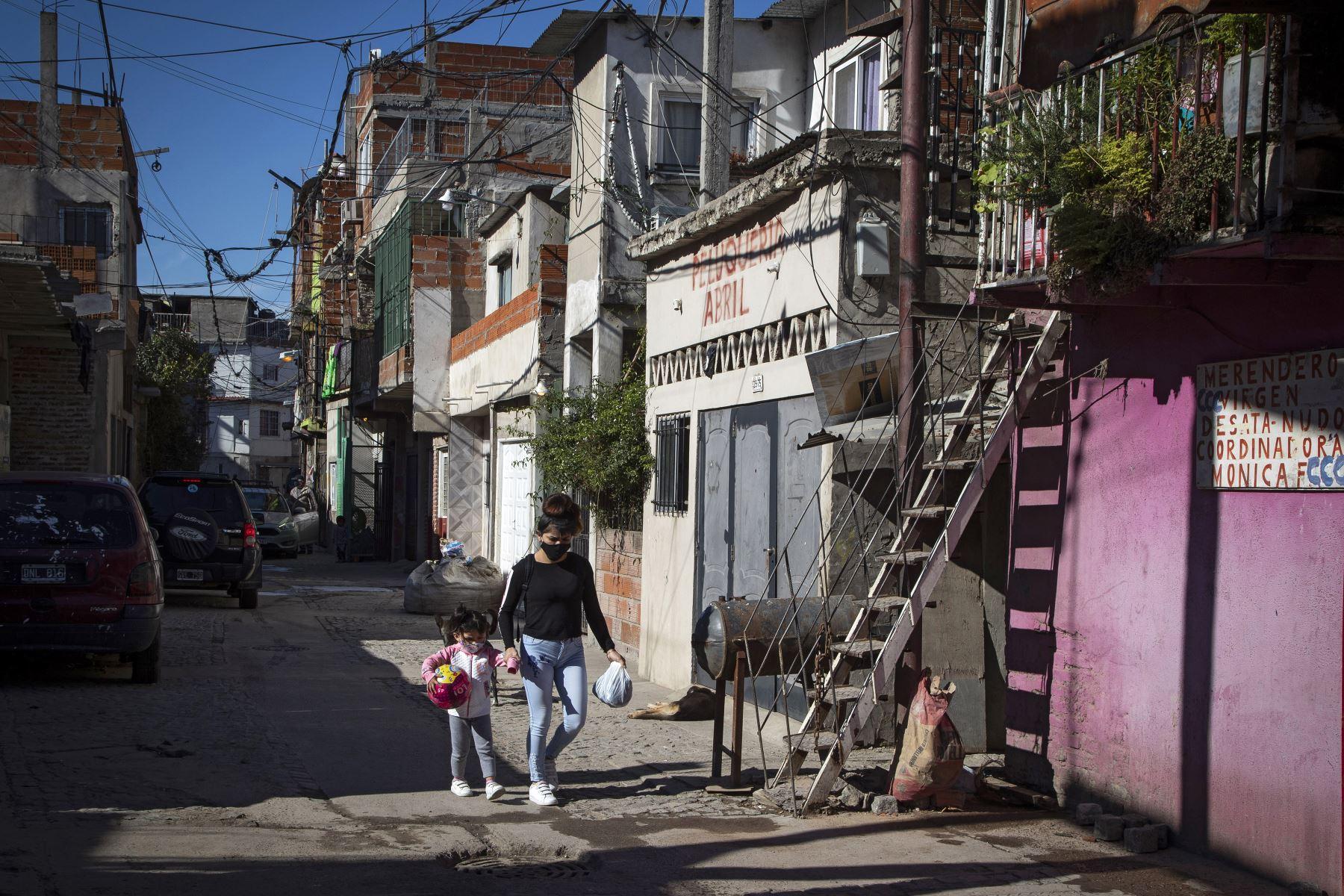 Una mujer y una niña caminan por un callejón en el barrio Padre Carlos Mugica, también conocido como Villa 31, en Buenos Aires. Foto: AFP