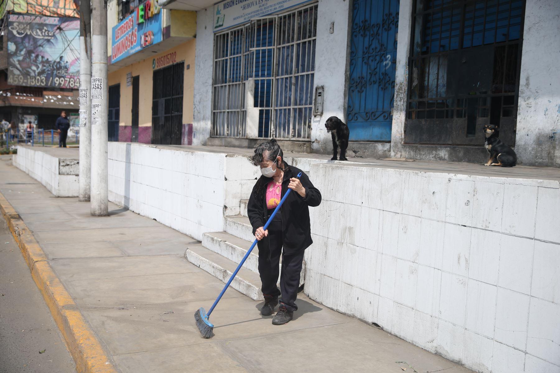 Una señora limpia los alrededores de su vivienda en San Juan de Lurigancho este domingo tras levantamiento de la inmovilización social obligatoria. Foto: ANDINA/Jhonel Rodríguez