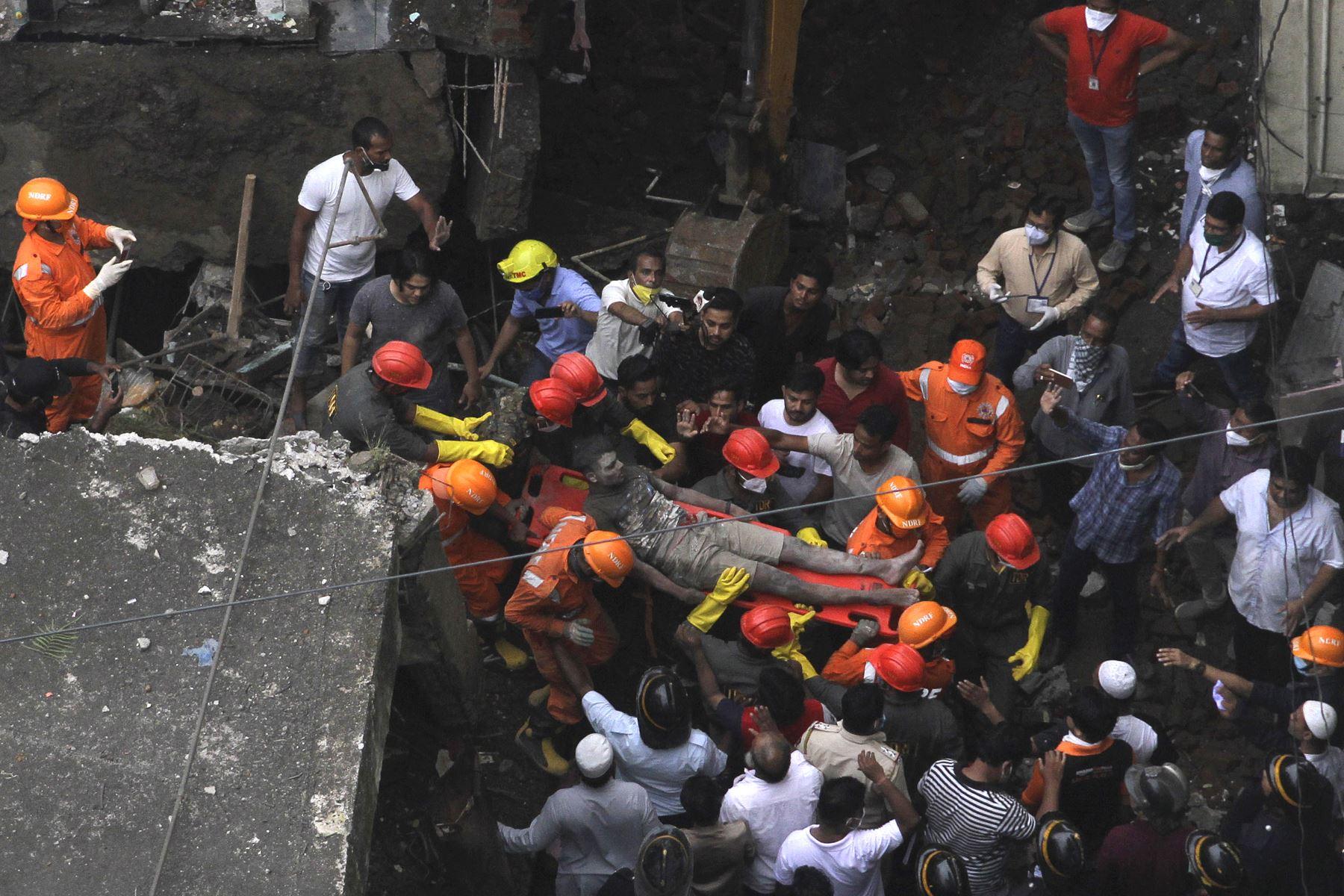 Los rescatistas trasladan a un sobreviviente de los escombros de un edificio residencial de tres pisos colapsado, en Bhiwandi, India. Foto: AFP