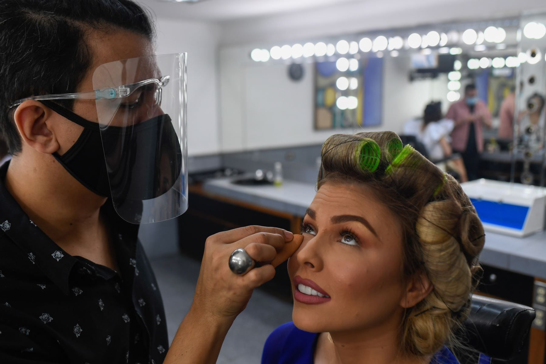 Una estilista con máscara y escudo facial, maquilla a la concursante de Miss Venezuela, en el camerino antes de una reunión con los jueces, en Caracas. Foto. AFP